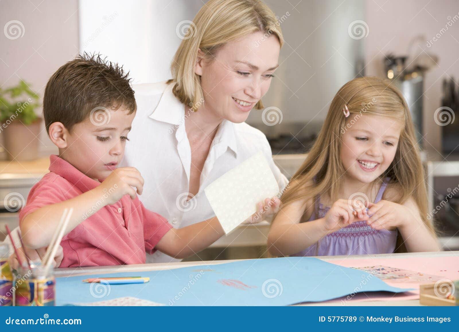 Mulher e duas crianças novas na cozinha com arte p