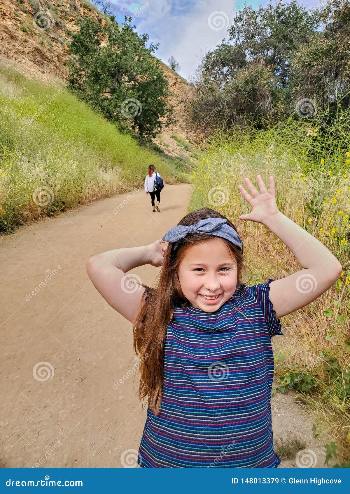 Mulher e filha que fazem as caras brincalhão ao andar junto em uma fuga ou em uma estrada de terra nas madeiras ao lado de um cam