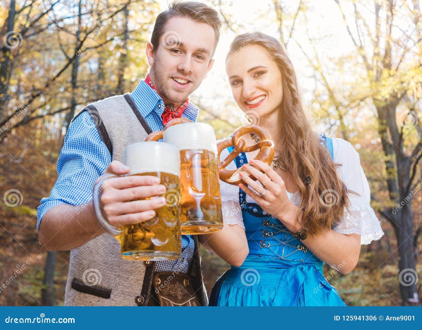 Mulher e homem na cerveja bebendo bávara de Tracht