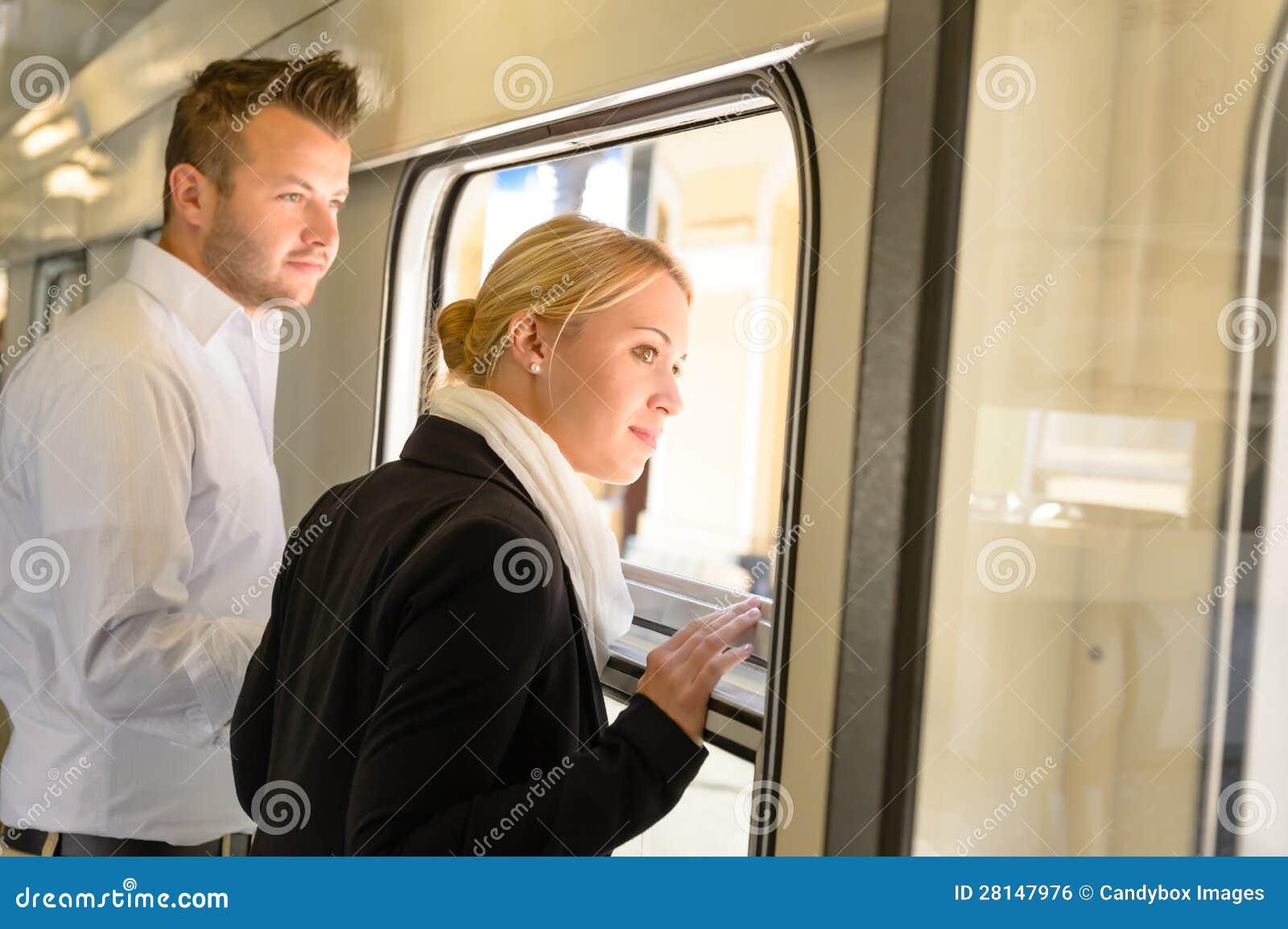 Mulher e homem que olham para fora o indicador do trem