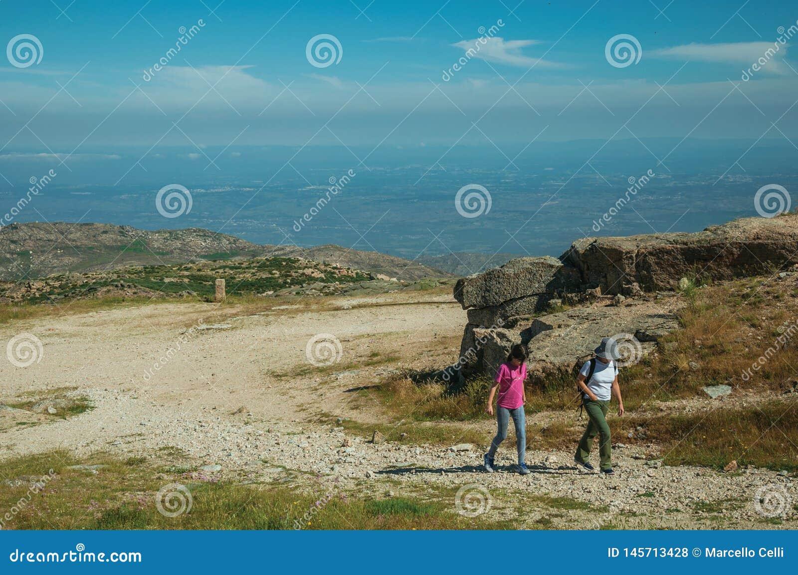 Mulher e menina que andam acima em uma fuga em montanhas