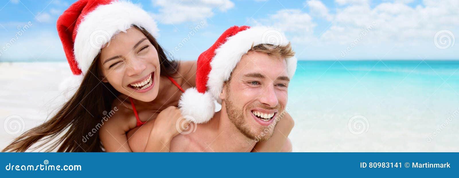 A mulher e o homem do feriado do Natal feliz acoplam a bandeira