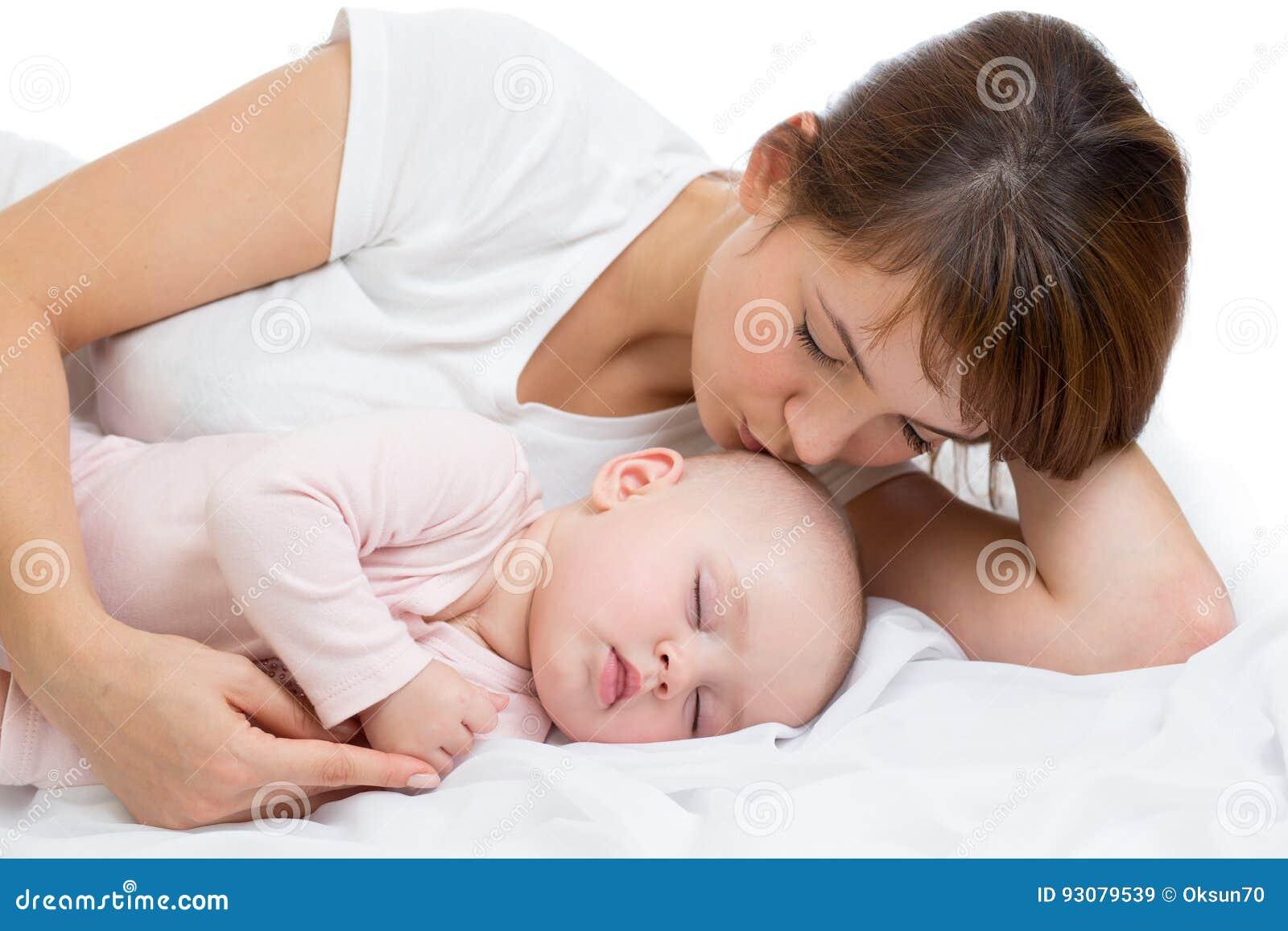 A mulher e o menino recém-nascido relaxam em um quarto branco Mãe nova que beija sua criança recém-nascida Bebê dos cuidados da m
