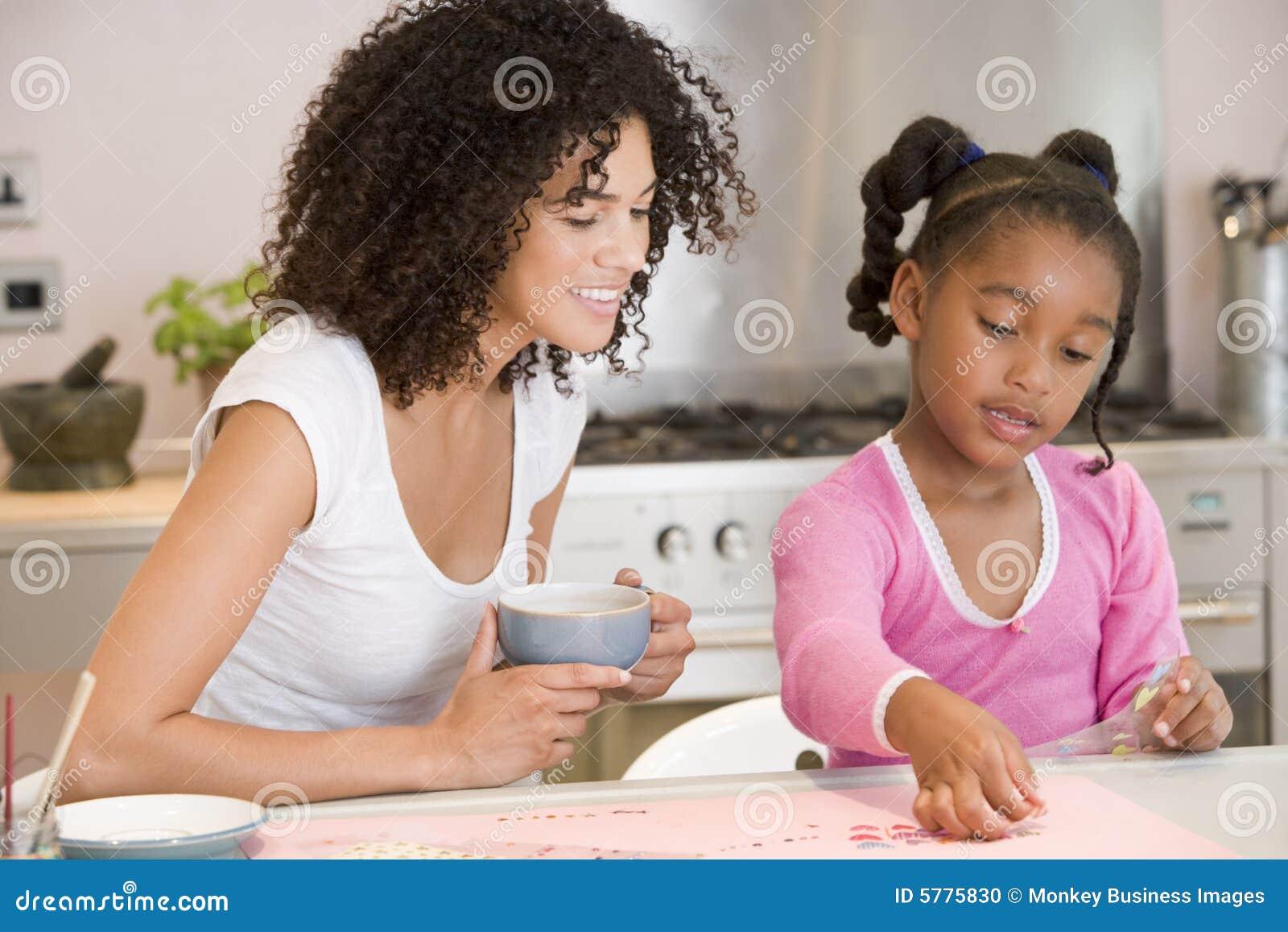 A mulher e a rapariga na cozinha com arte projetam s