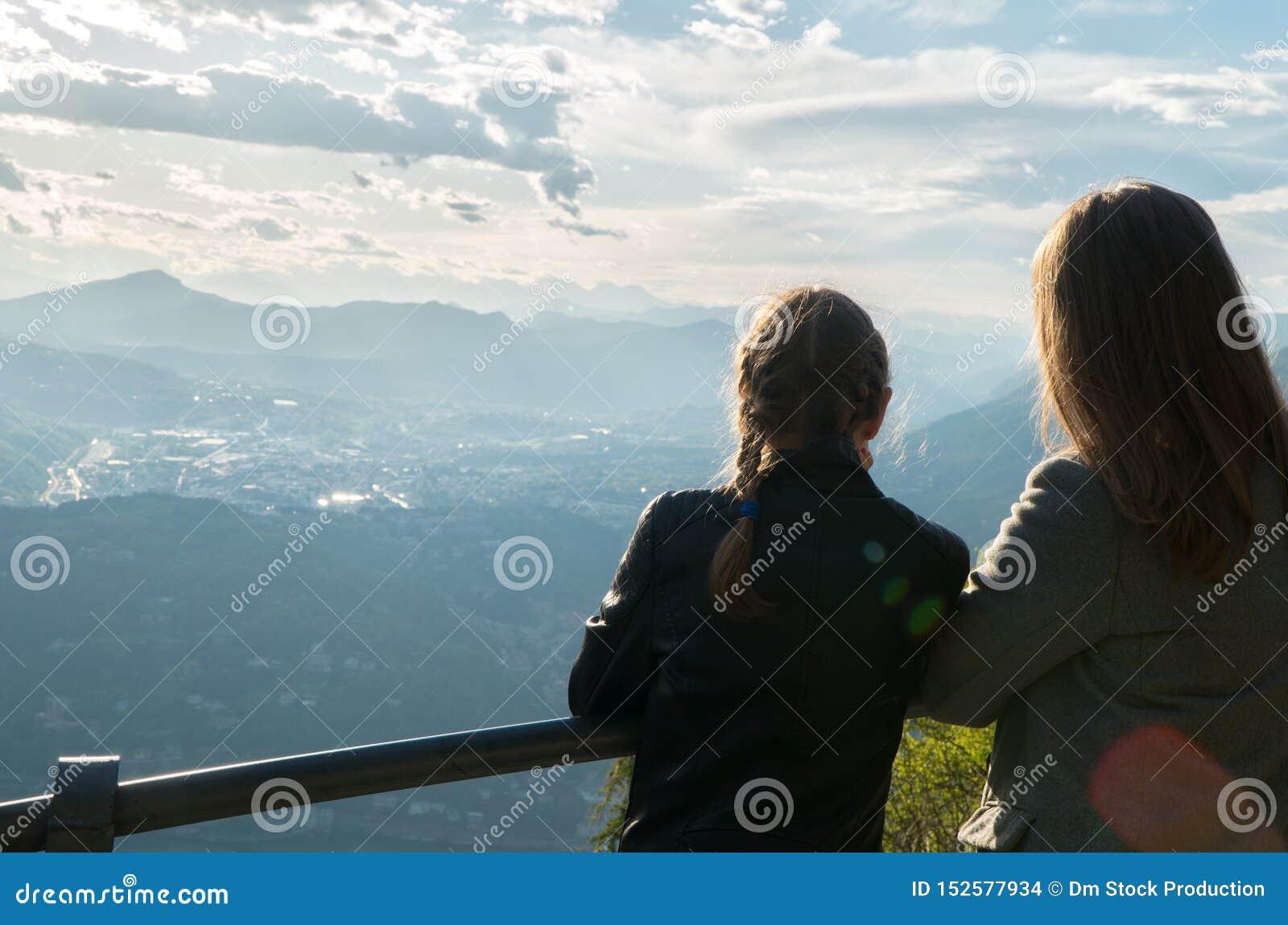 Mulher e sua filha que apreciam o nascer do sol da parte superior da montanha