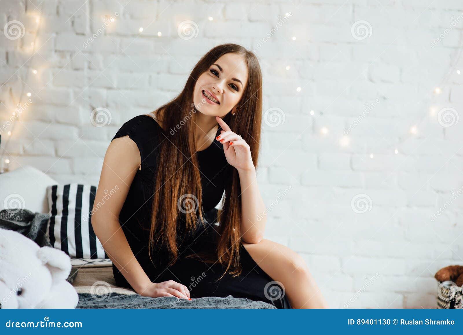 Mulher elegante com as cintas no vestido preto