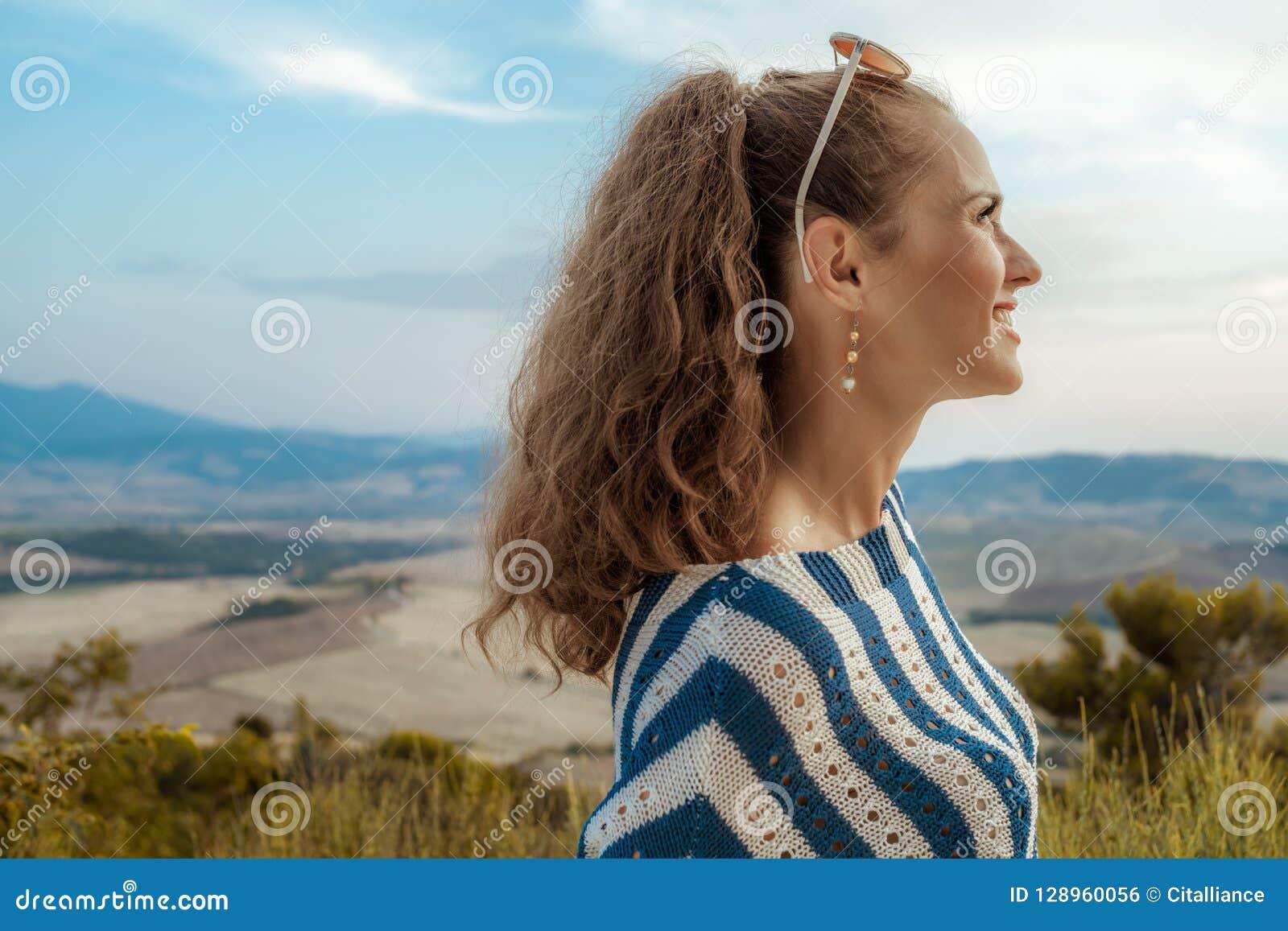 Mulher elegante de sorriso do turista que olha na distância
