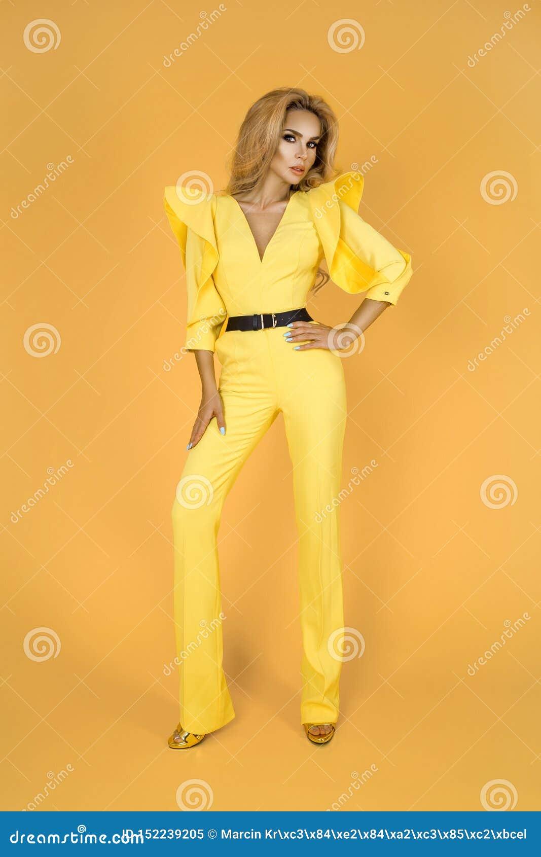 Mulher elegante no fato-macaco, em sapatas e em acessórios amarelos agradáveis Foto do verão da mola da forma - imagem