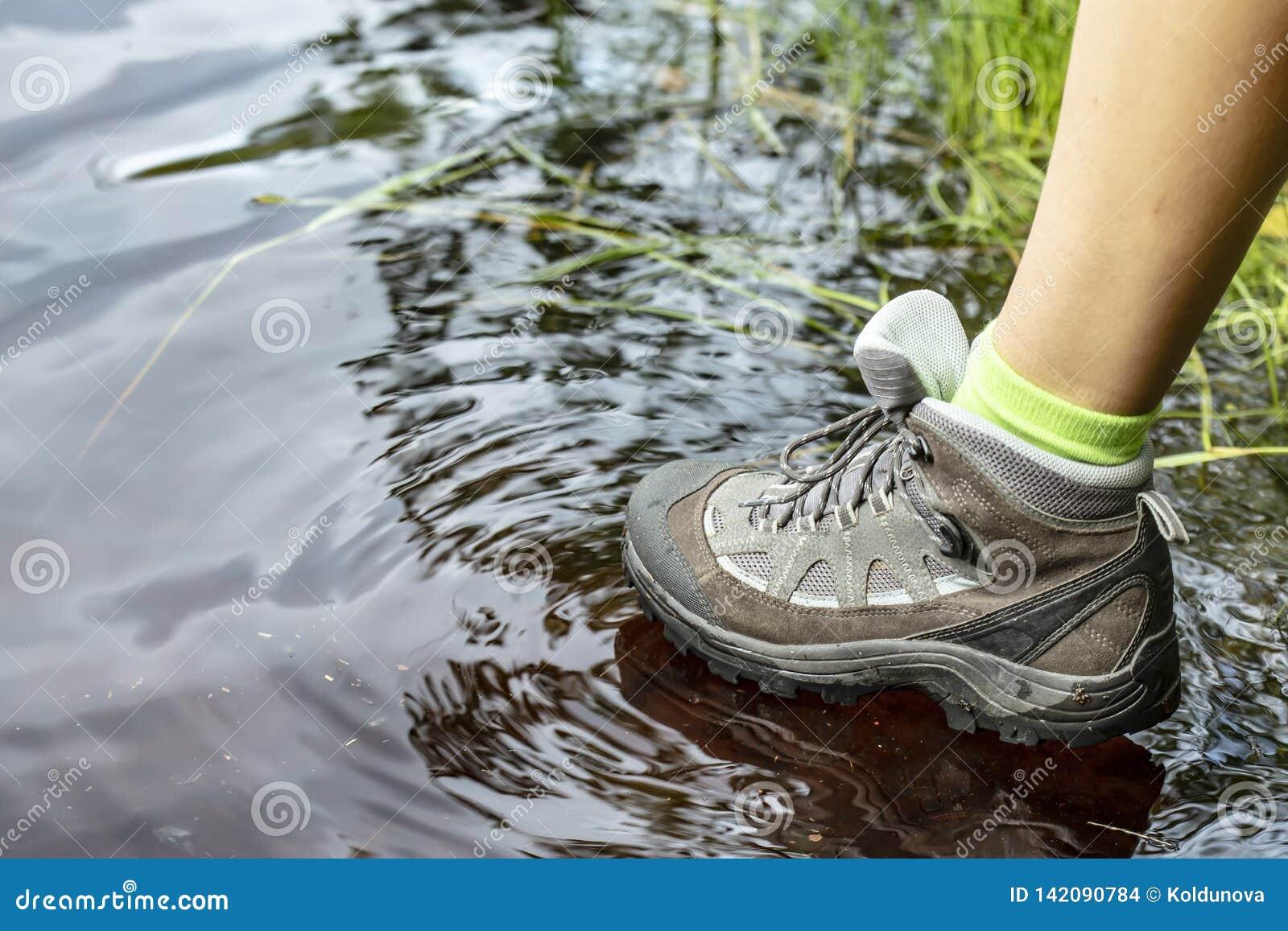 Mulher em caminhadas de caminhada impermeáveis das botas do turista através da água nas poças