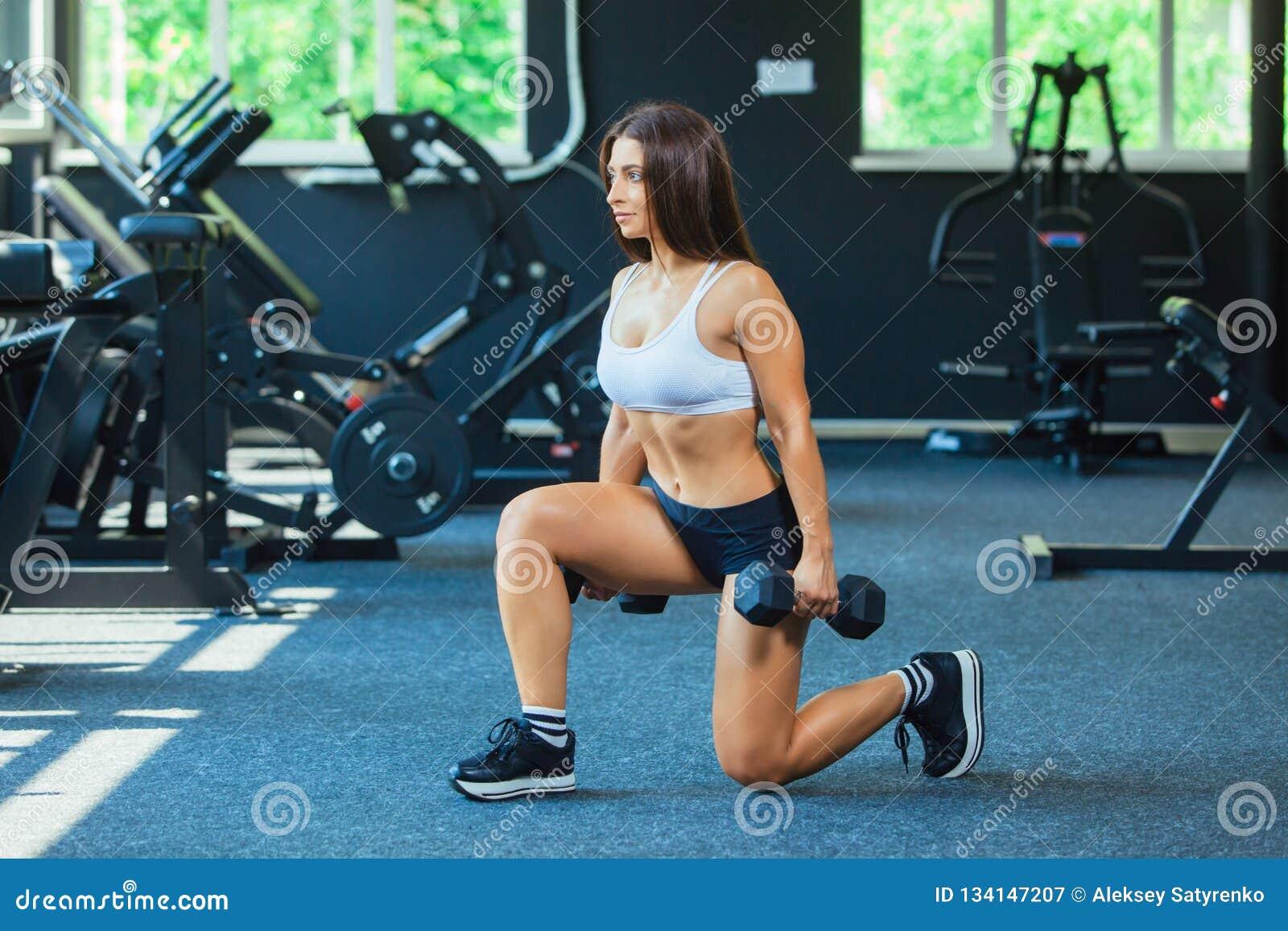 A mulher em esportes da forma veste o treinamento, fazendo investe contra o exercício com pesos no gym