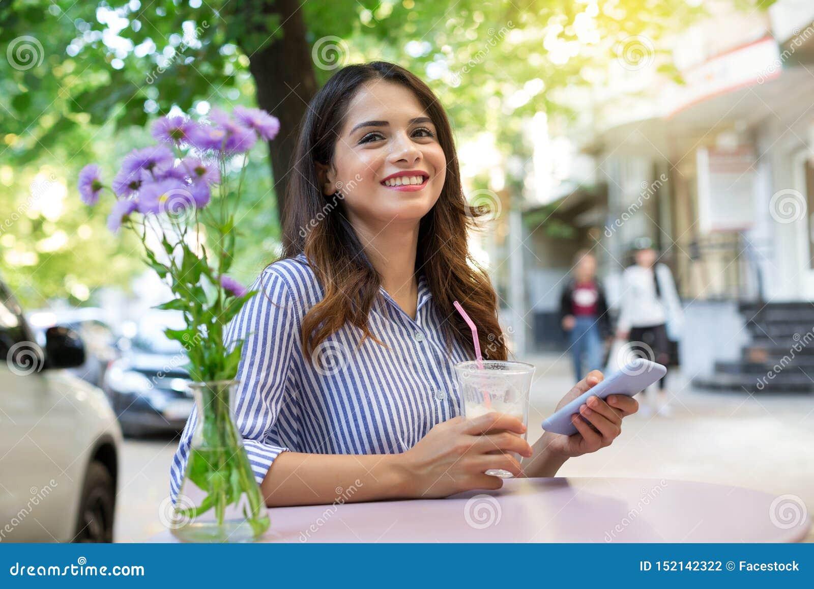 Mulher em um café bebendo do café, guardando um telefone e olhando a câmera Copie o espa?o