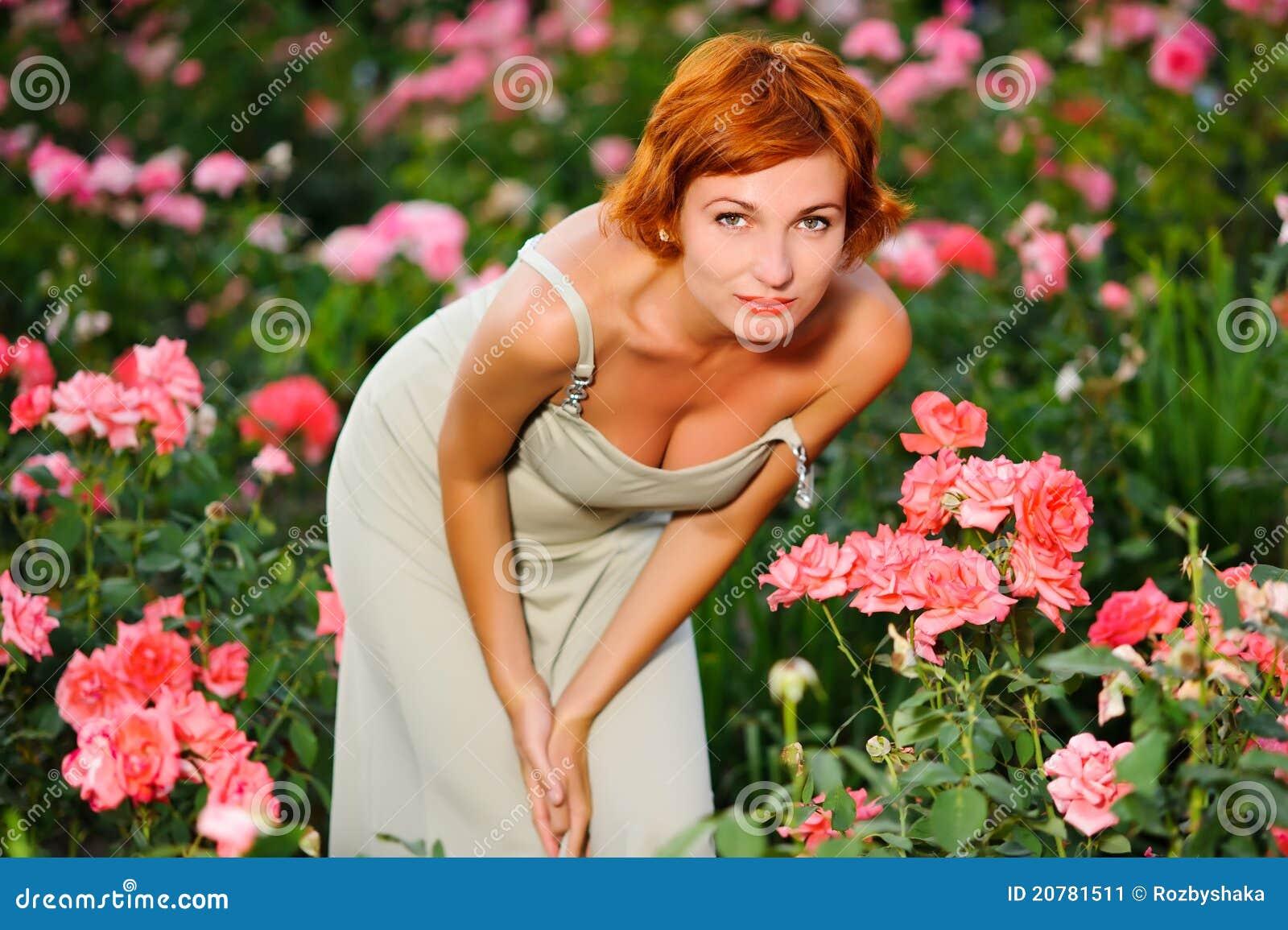 Mulher nova bonita em um jardim das rosas no dia de verão ensolarado