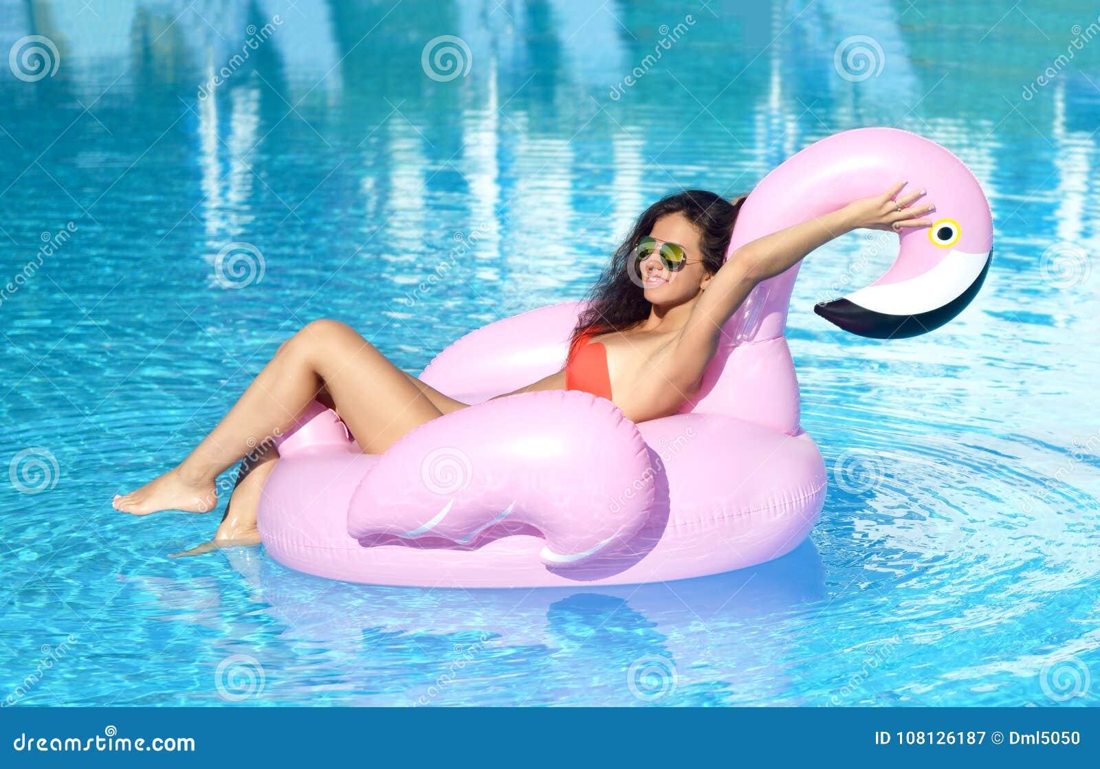 Mulher em um lazer da piscina em um colchão cor-de-rosa gigante inflável gigante do flutuador do flamingo no biquini vermelho