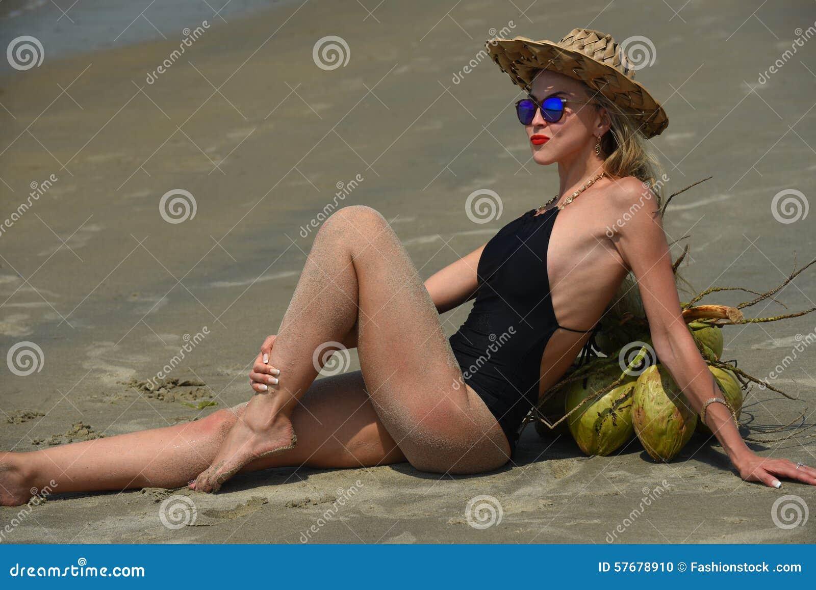 Mulher em um roupa de banho e em um chapéu pretos que relaxam na praia tropical
