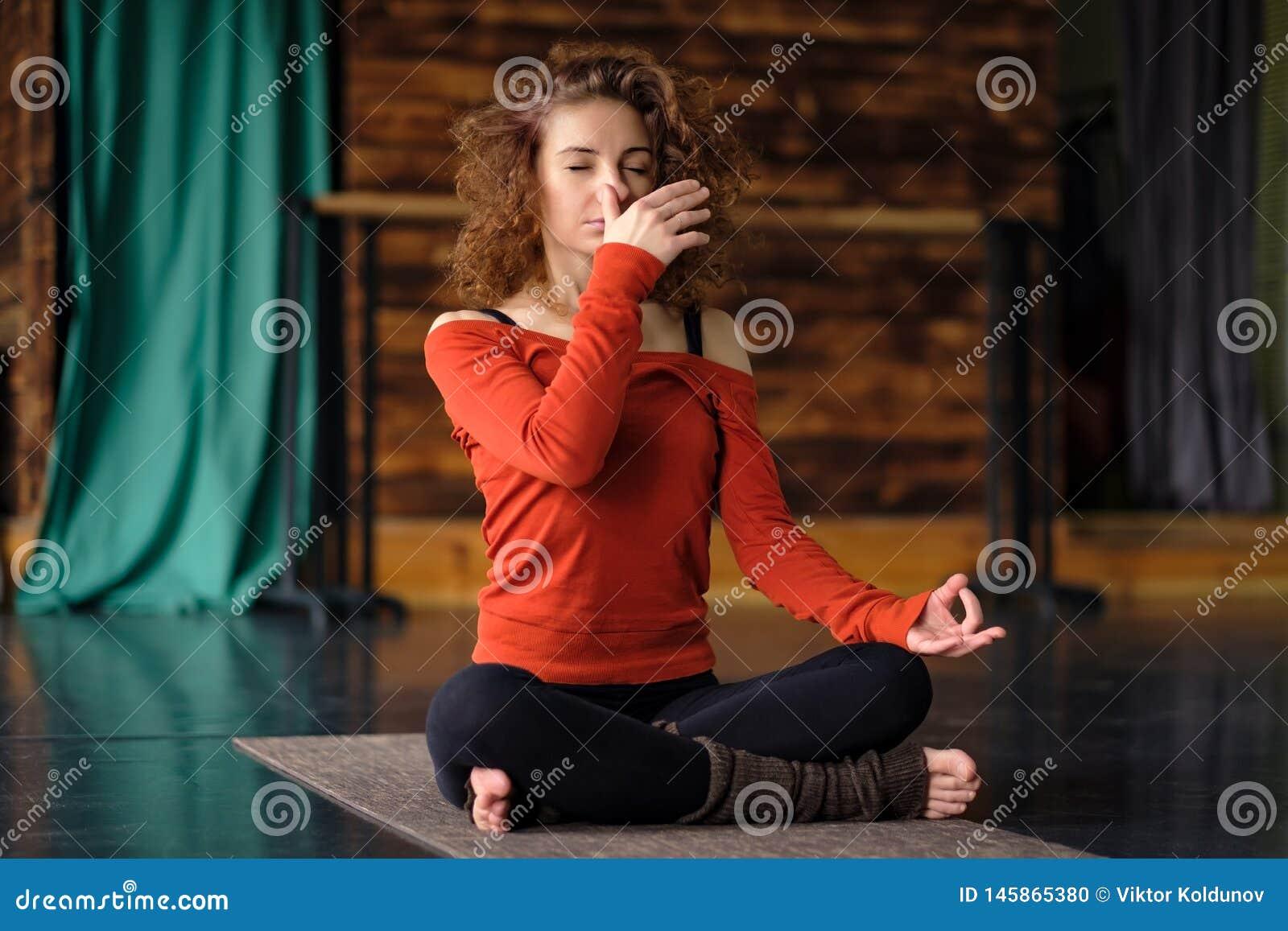 Mulher encaracolado nova que faz exercícios da ioga, usando o pranayama do shodhana do nadi