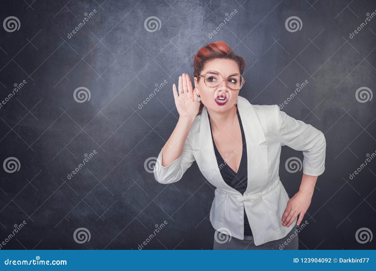 A mulher engraçada bisbilhota no fundo do quadro-negro
