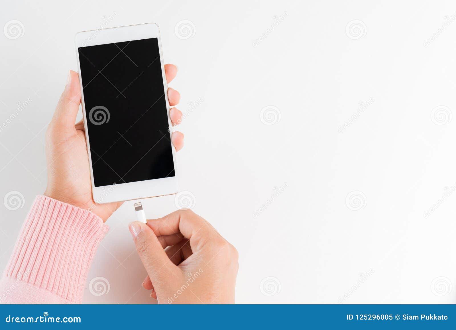A mulher entrega o carregador de conexão ao smartphone na parte traseira branca da tabela