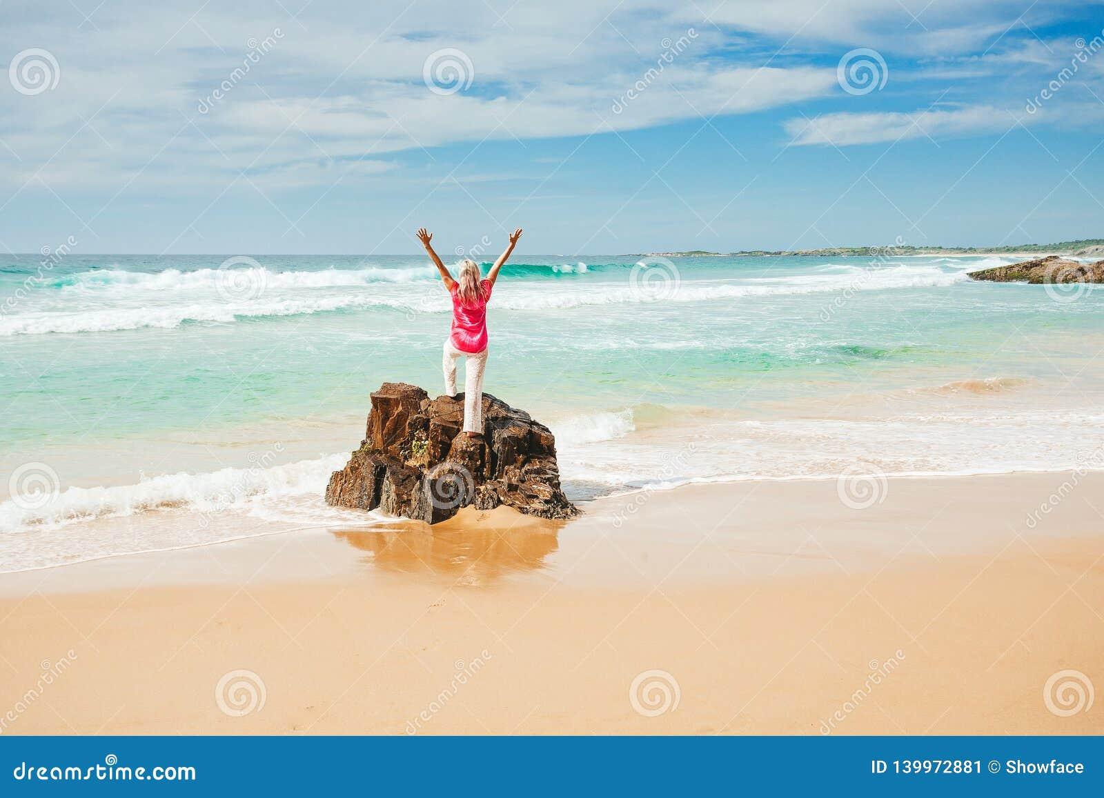 A mulher entusiasmada ama a vida do beac, dia ensolarado bonito