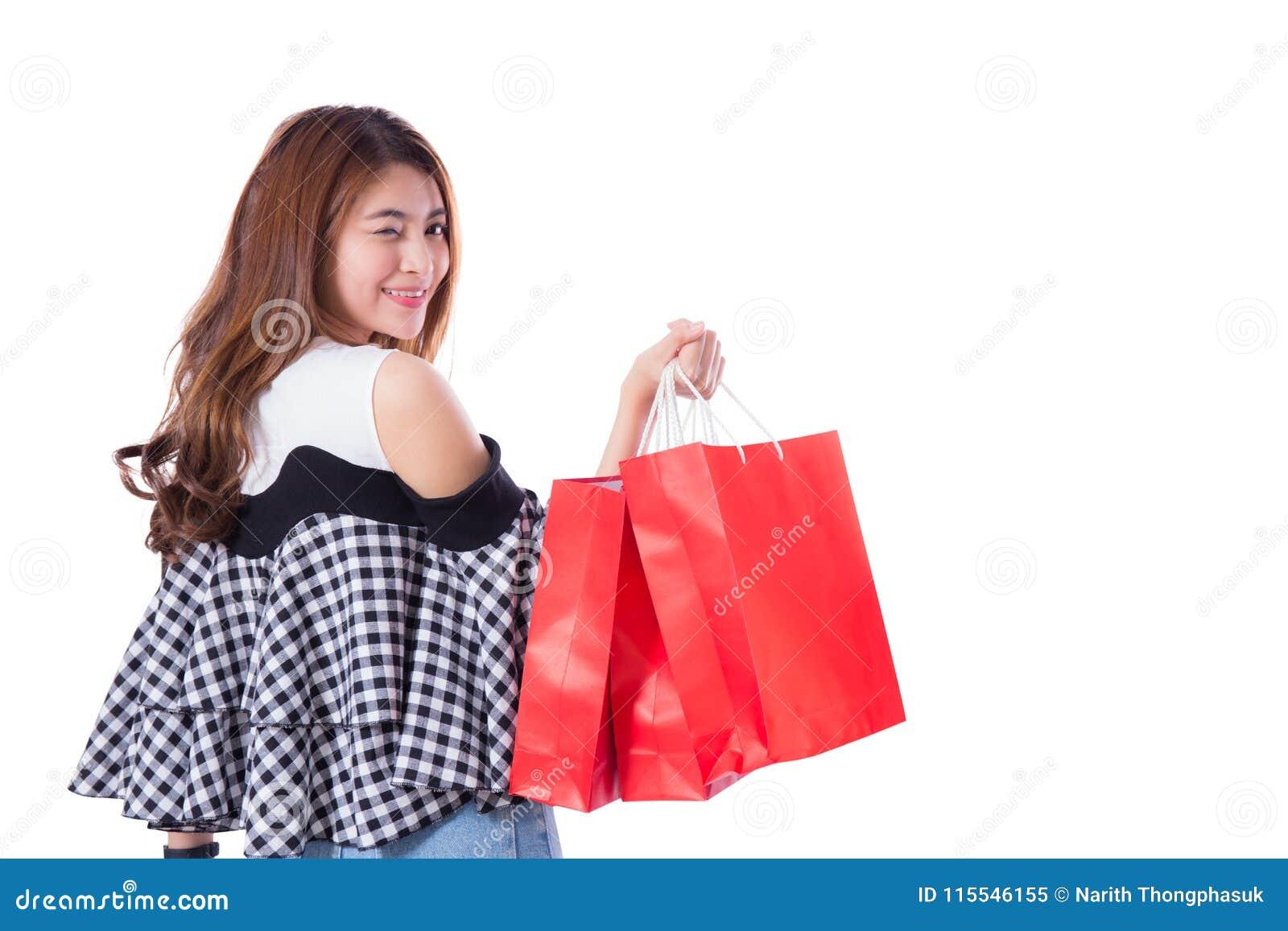 Mulher entusiasmado feliz que está e que mantém sacos de compras coloridos isolados