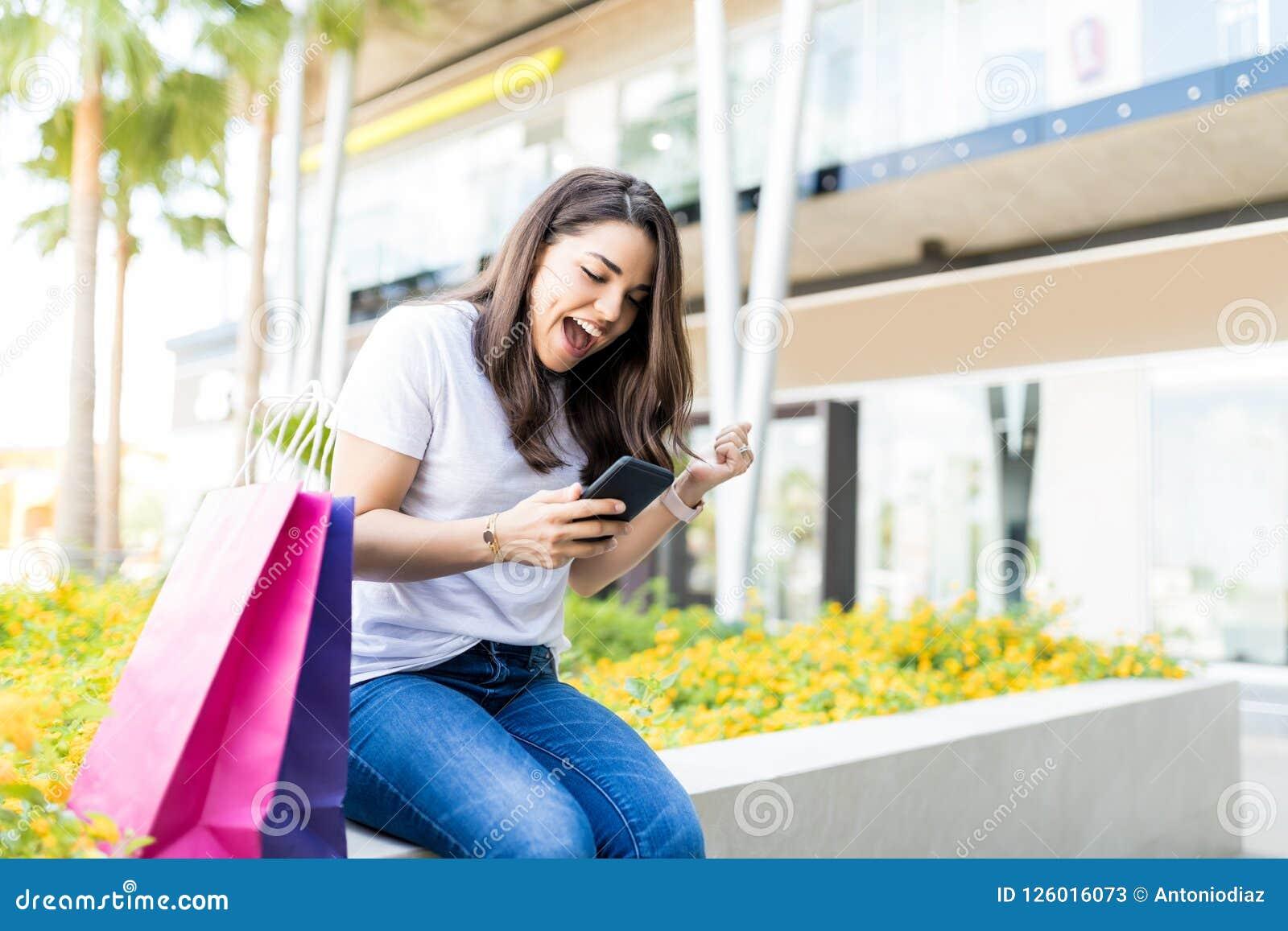 Mulher entusiasmado que usa Smartphone por sacos de compras fora da alameda