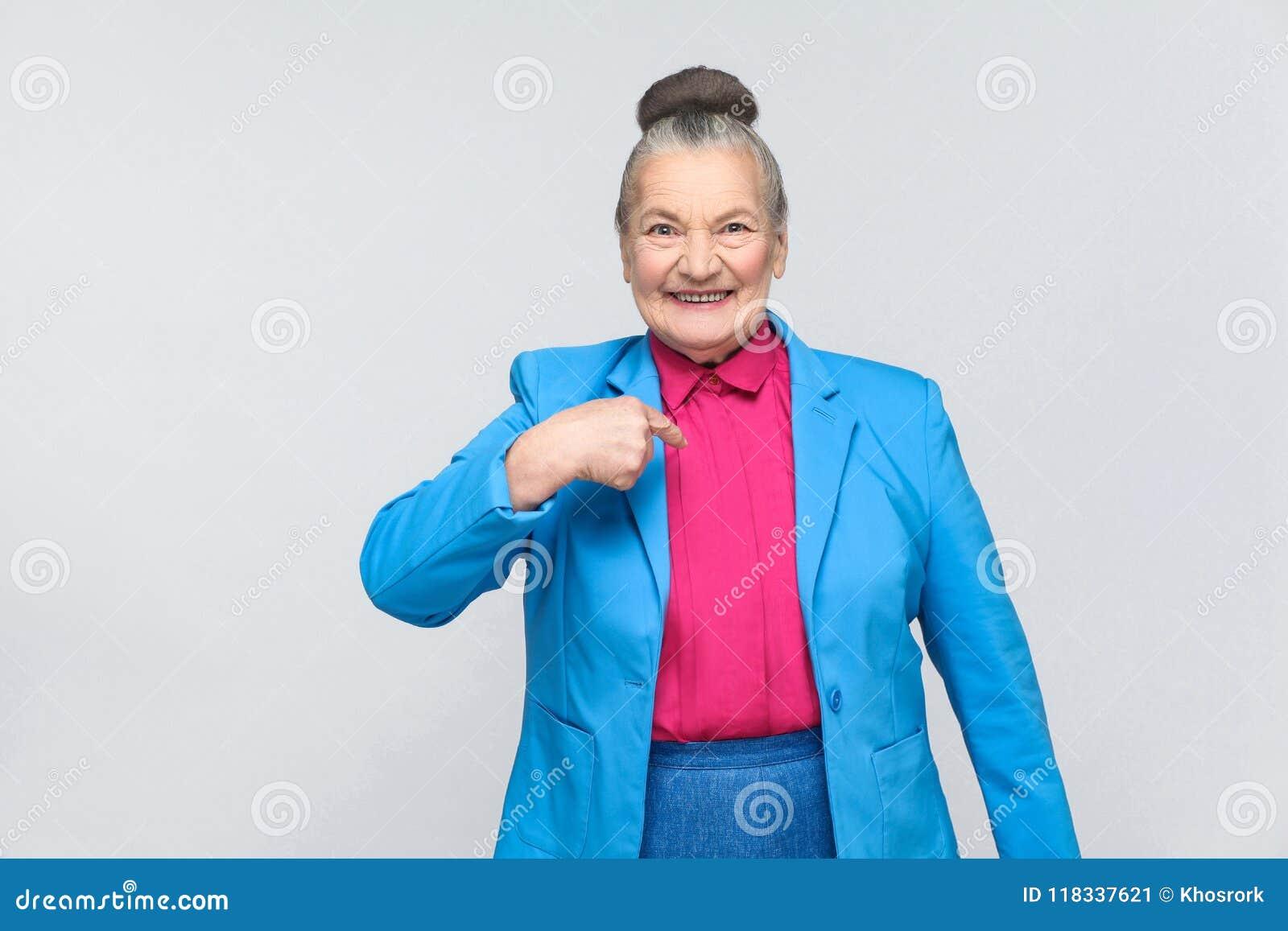 Mulher envelhecida que aponta o dedo ela mesma e sorriso toothy