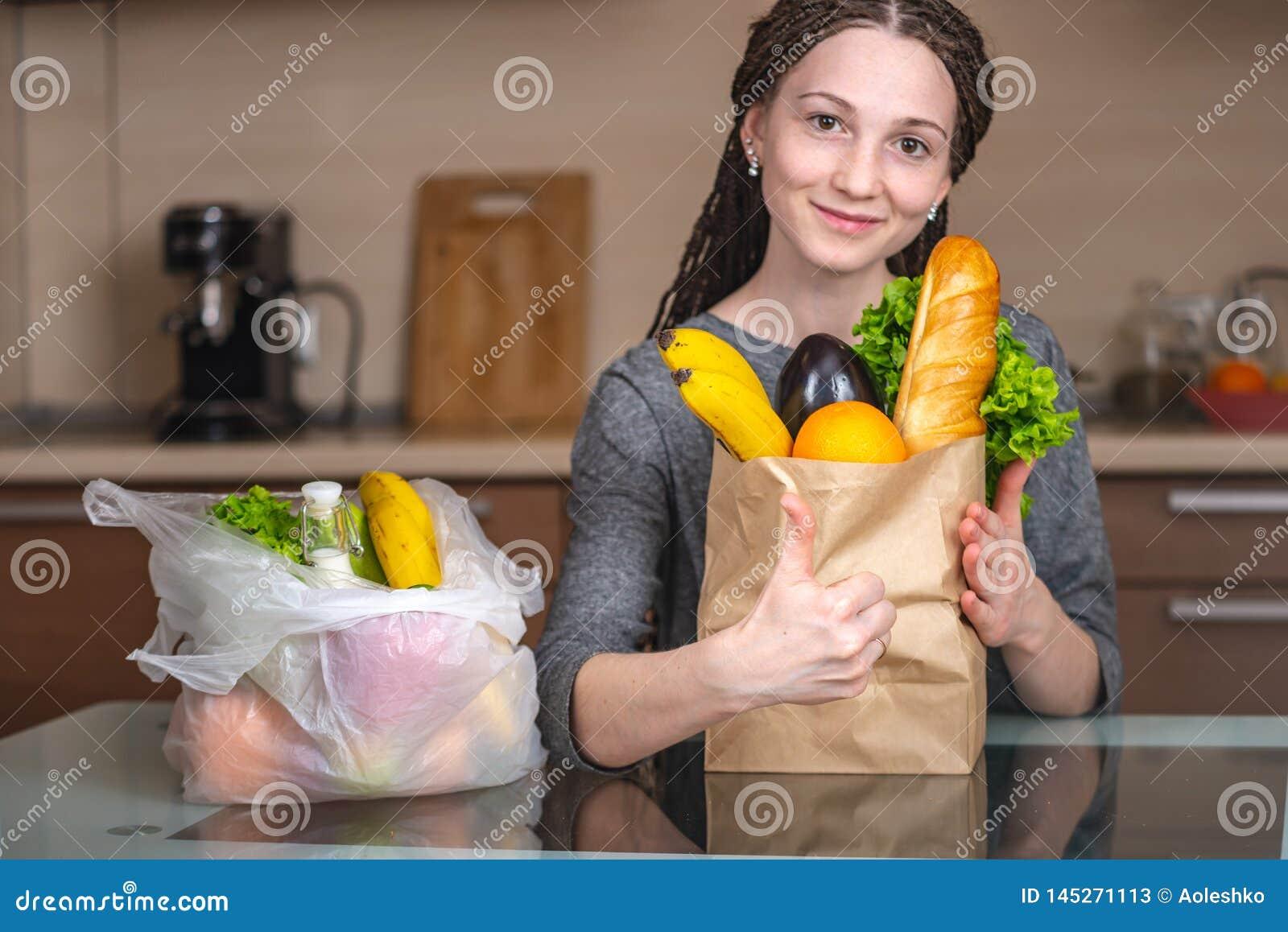 A mulher escolhe um saco de papel com alimento e recusa-o usar o plástico Conceito da prote