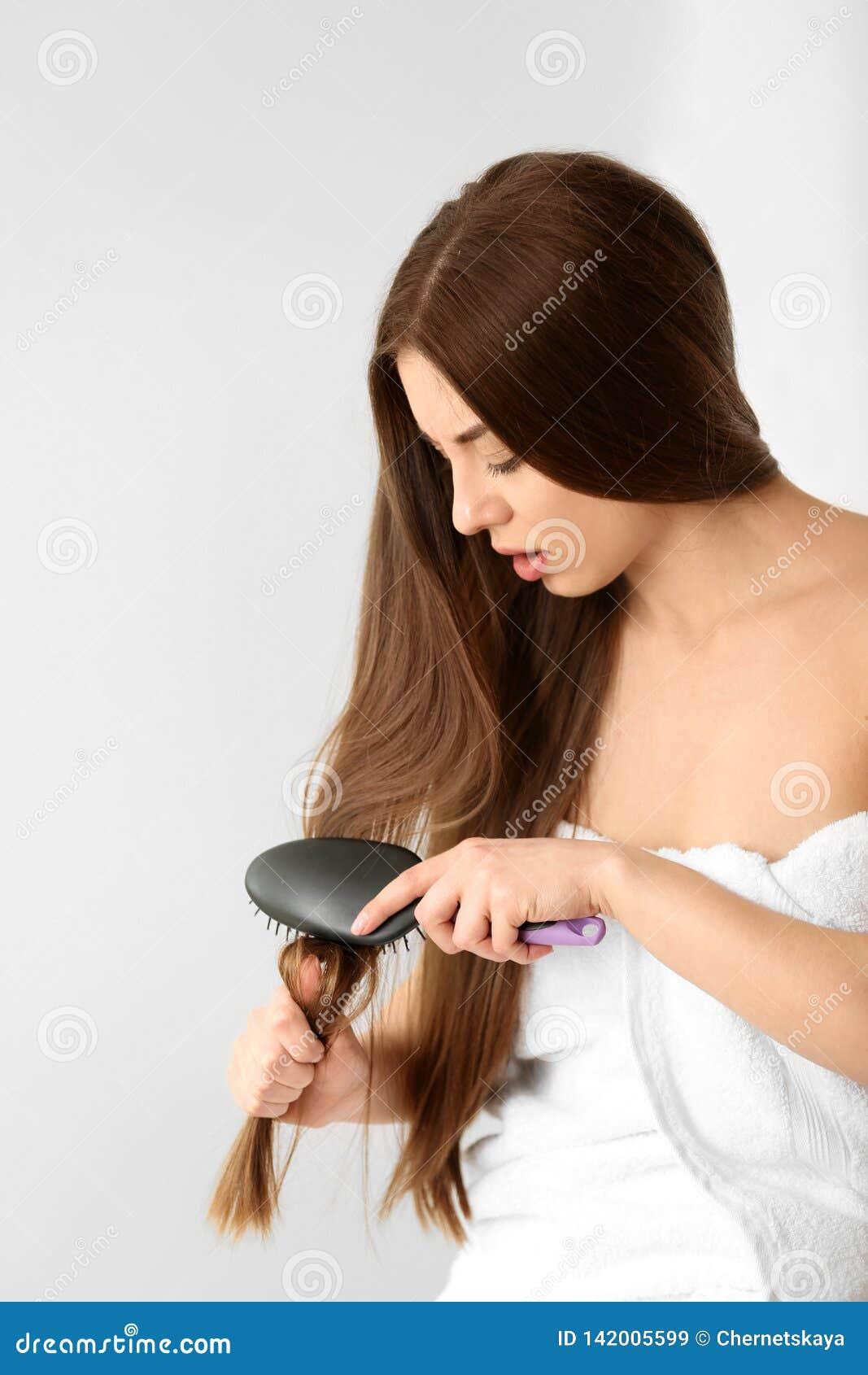 A mulher esforça-se para escovar seu cabelo