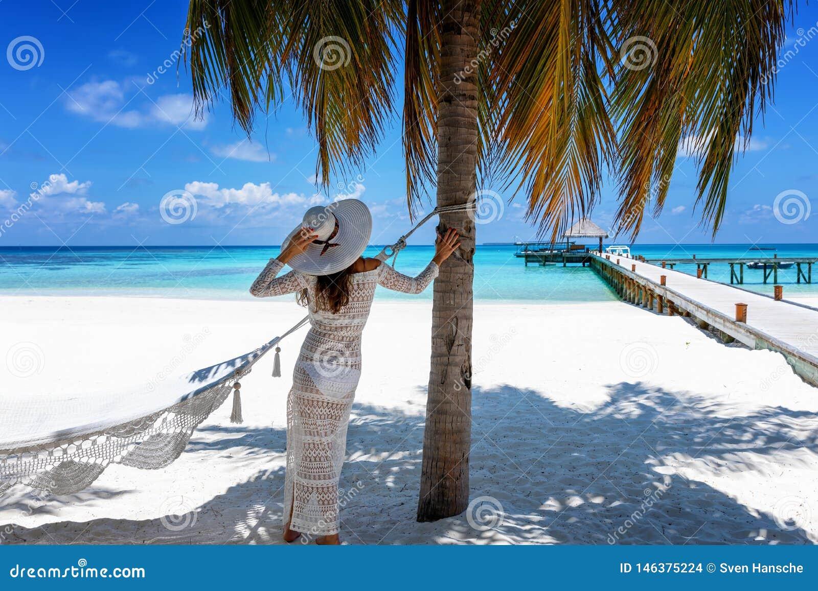 A mulher está em uma praia tropical do paraíso em Maldivas