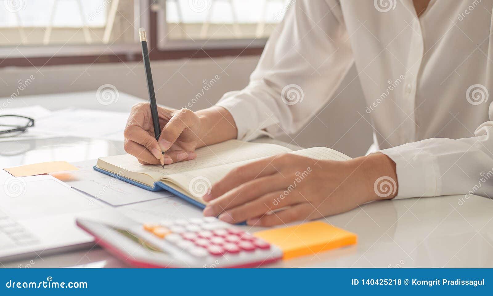 A mulher está escrevendo uma mensagem no livro na tabela