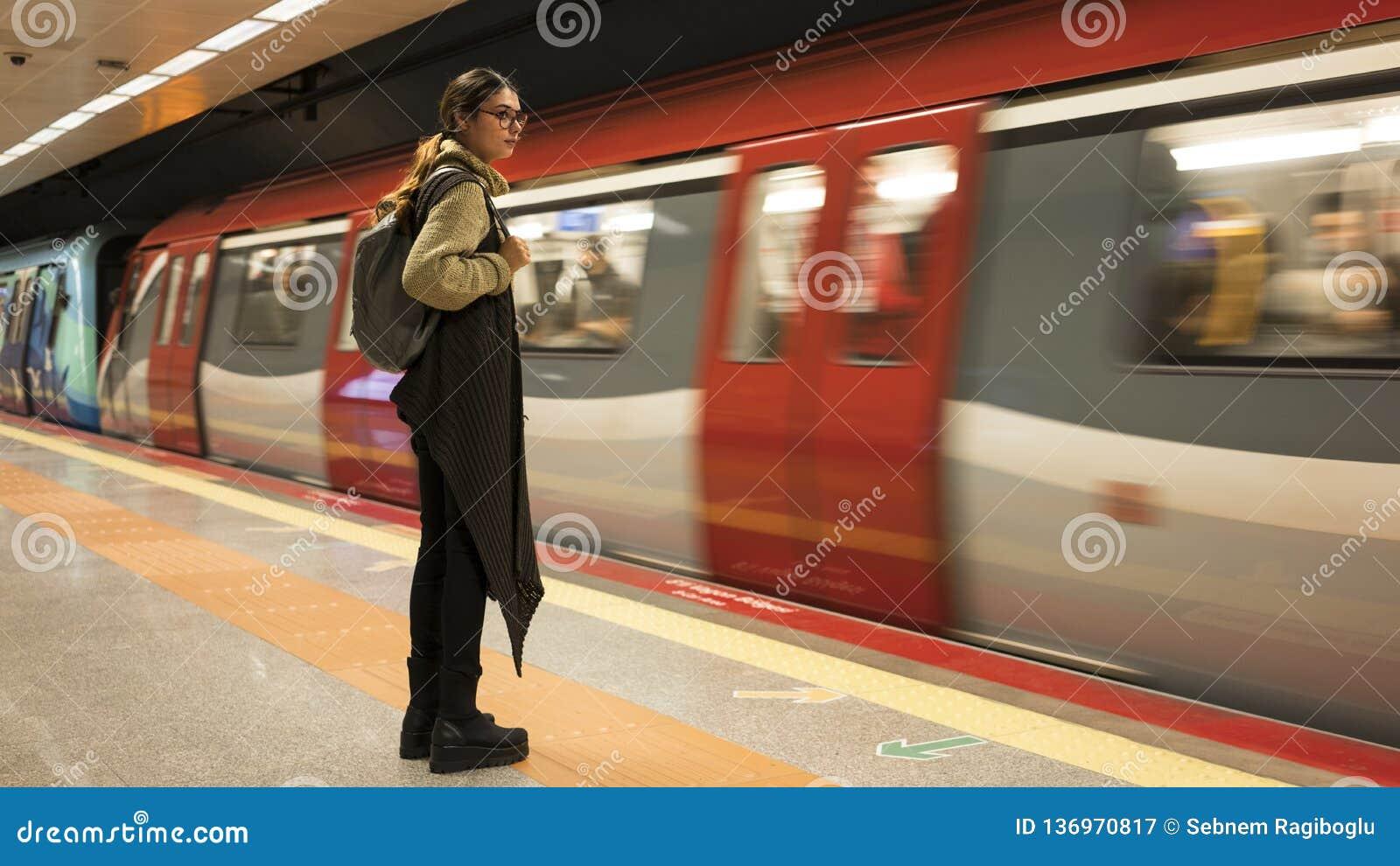 A mulher está esperando o trem no metro