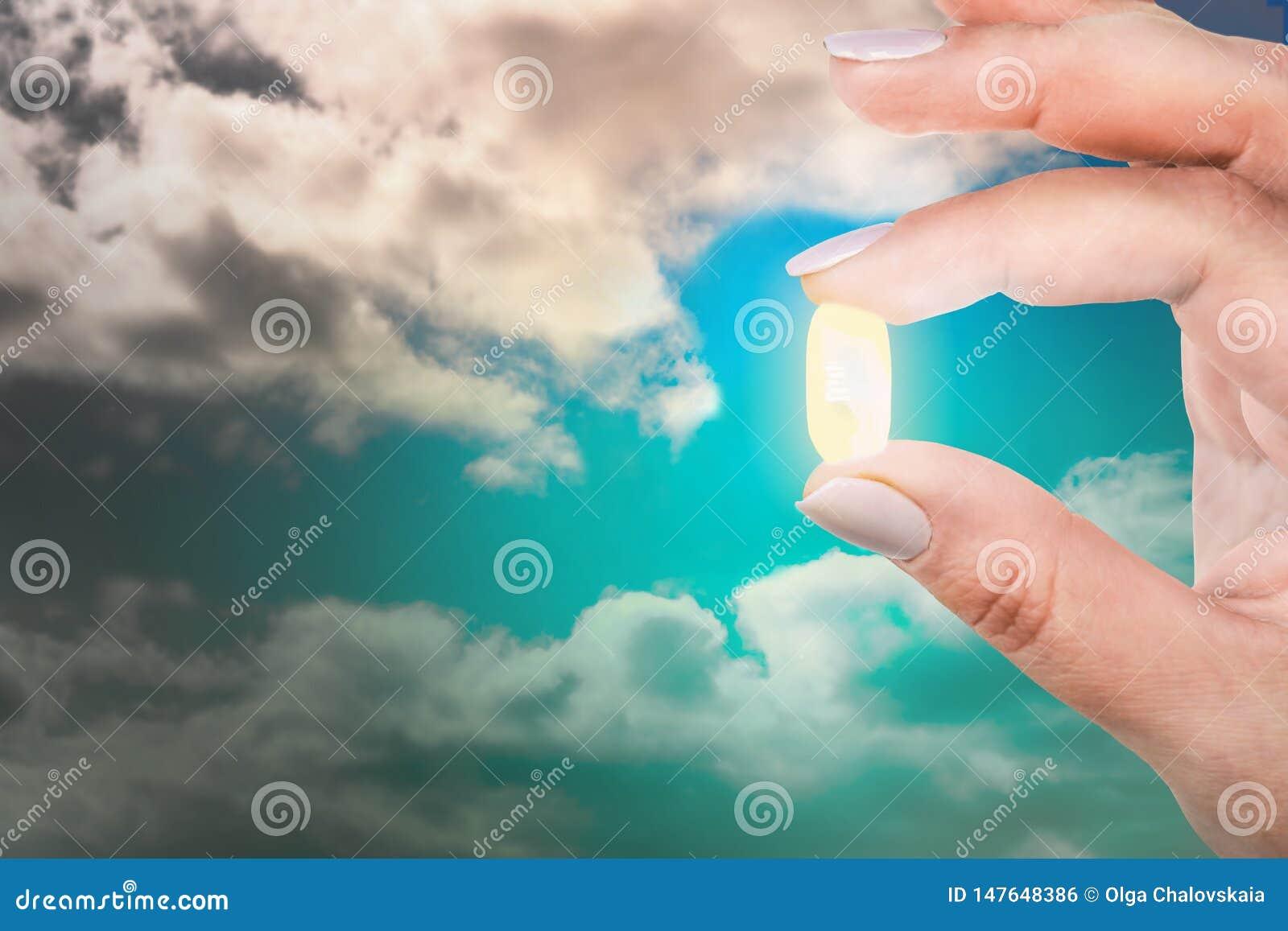 A mulher está mantendo seus dedos uma cápsula do antidepressivo contra o céu azul Saída da depressão