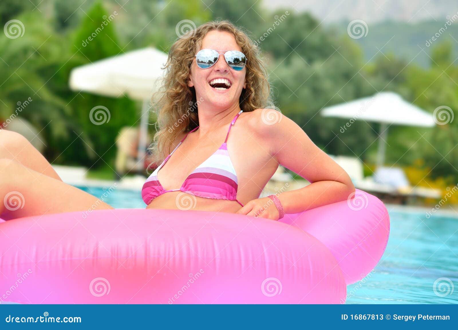 A mulher está nadando em uma associação na cama de ar