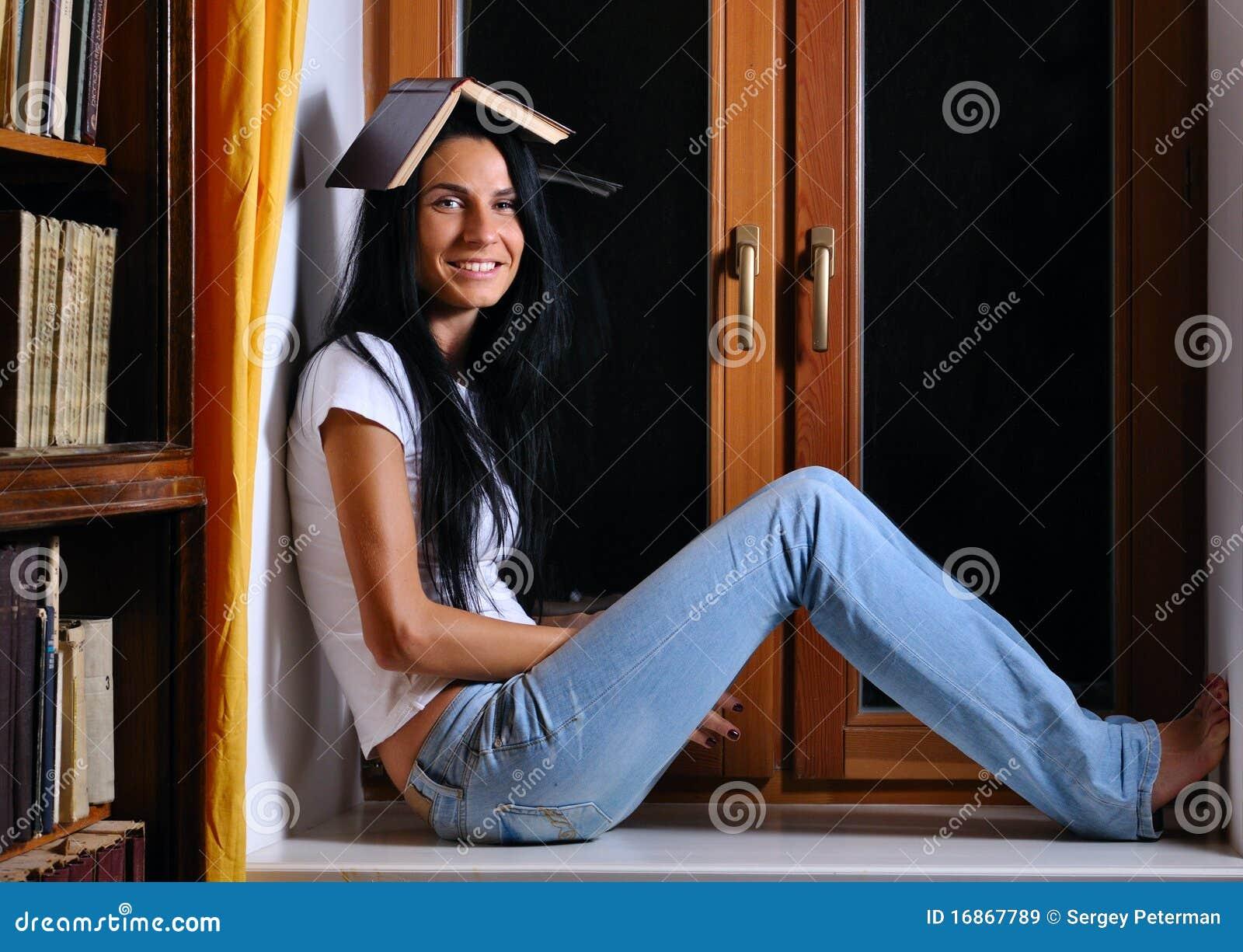 A mulher está sentando-se no indicador com livro