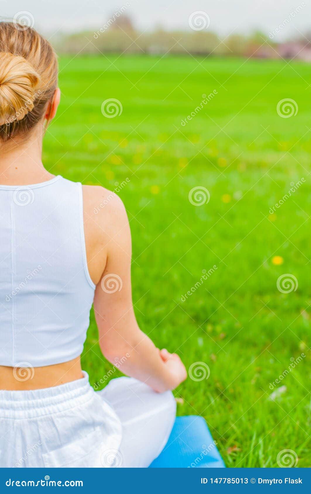 A mulher est? meditando o assento na pose de Lotus na grama no parque