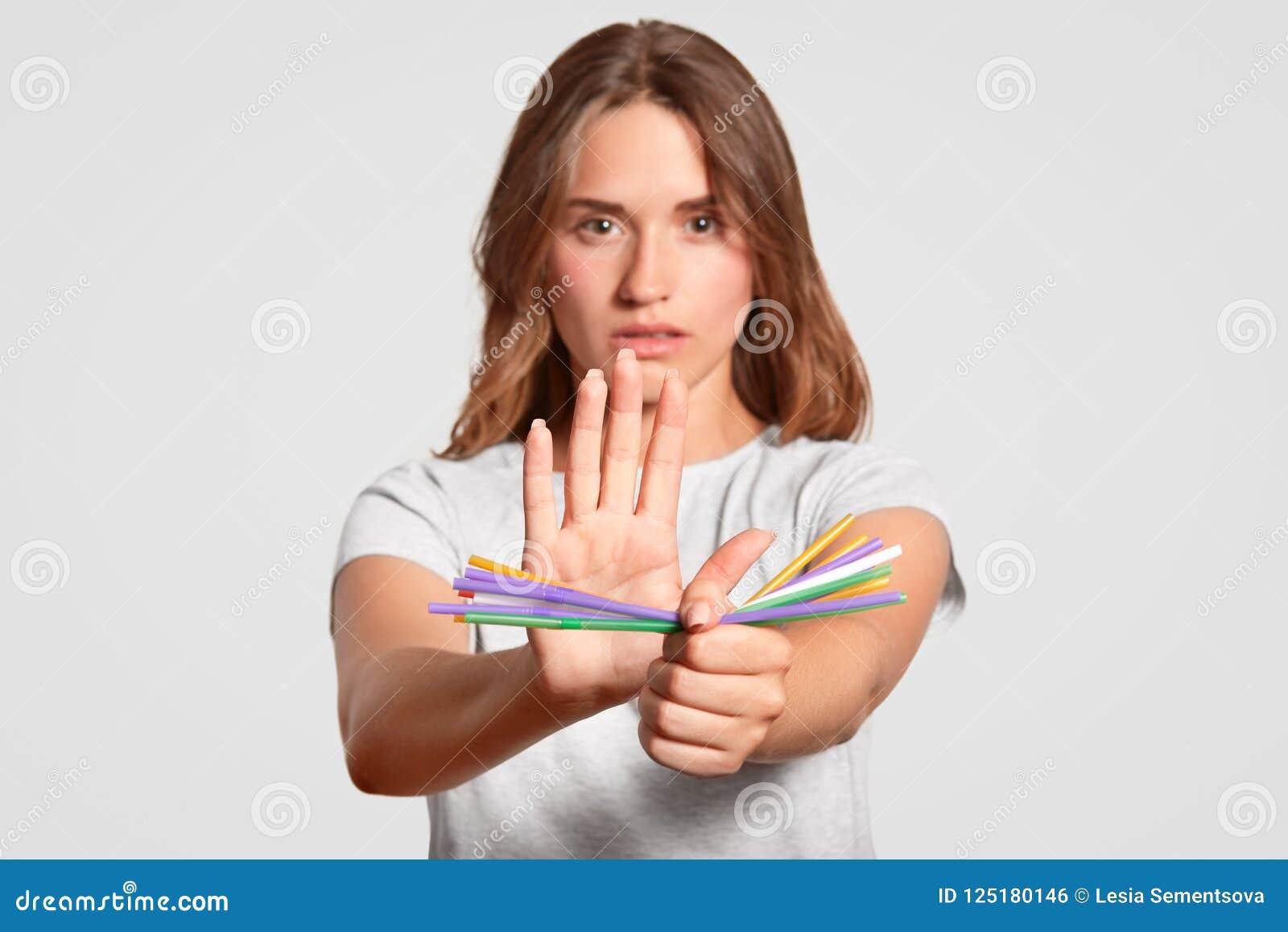 A mulher europeia com expressão séria, palhas plásticas das posses, diz não às palhas bebendo plásticas descartáveis em favor de