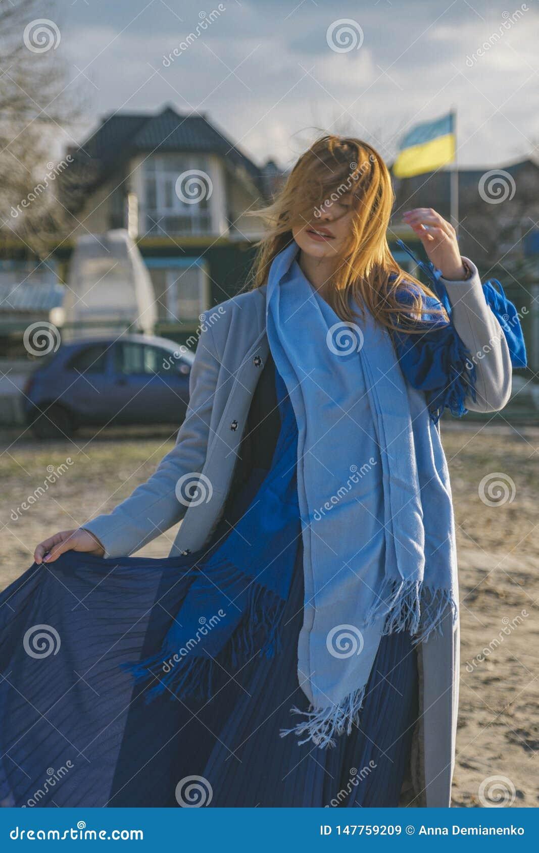 Mulher europeia lindo no revestimento e no vestido mornos em uma caminhada no parque perto do rio Tempo ventoso Sua roupa voa no