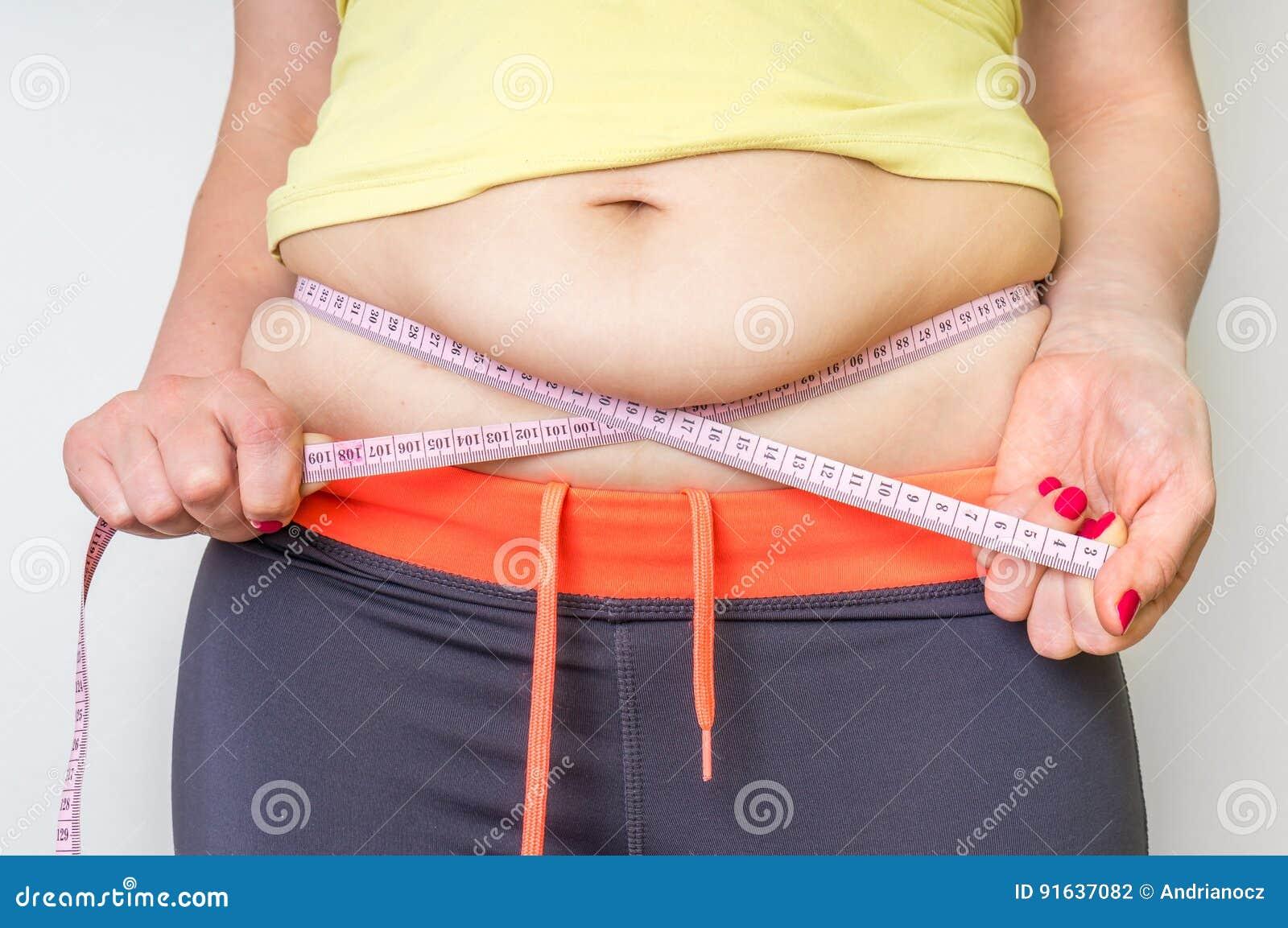 A mulher excesso de peso com fita está medindo a gordura na barriga