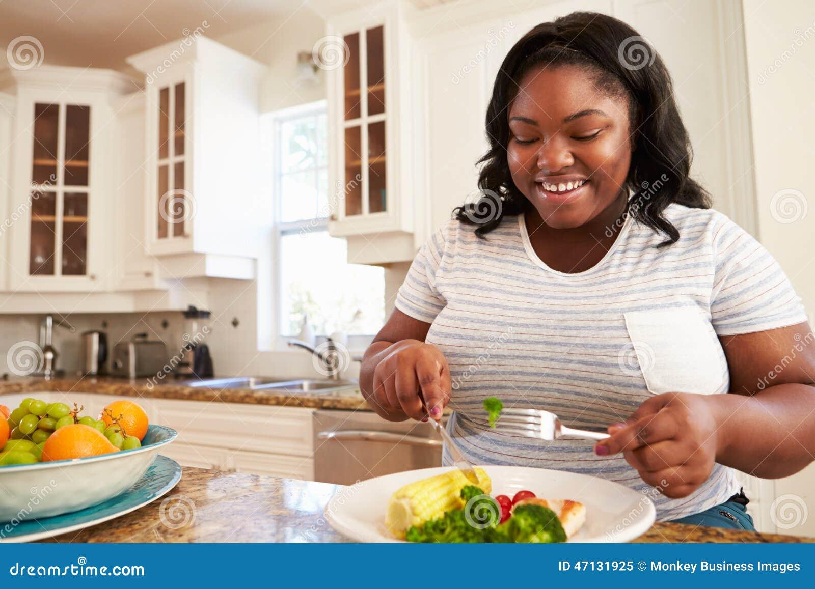 Mulher excesso de peso que come a refeição saudável na cozinha