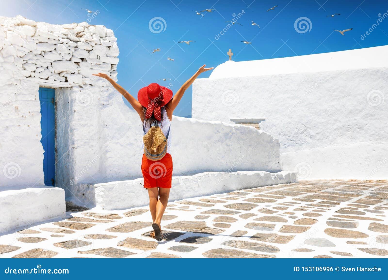 A mulher explora as aleias brancas das ilhas de Cyclades de Grécia