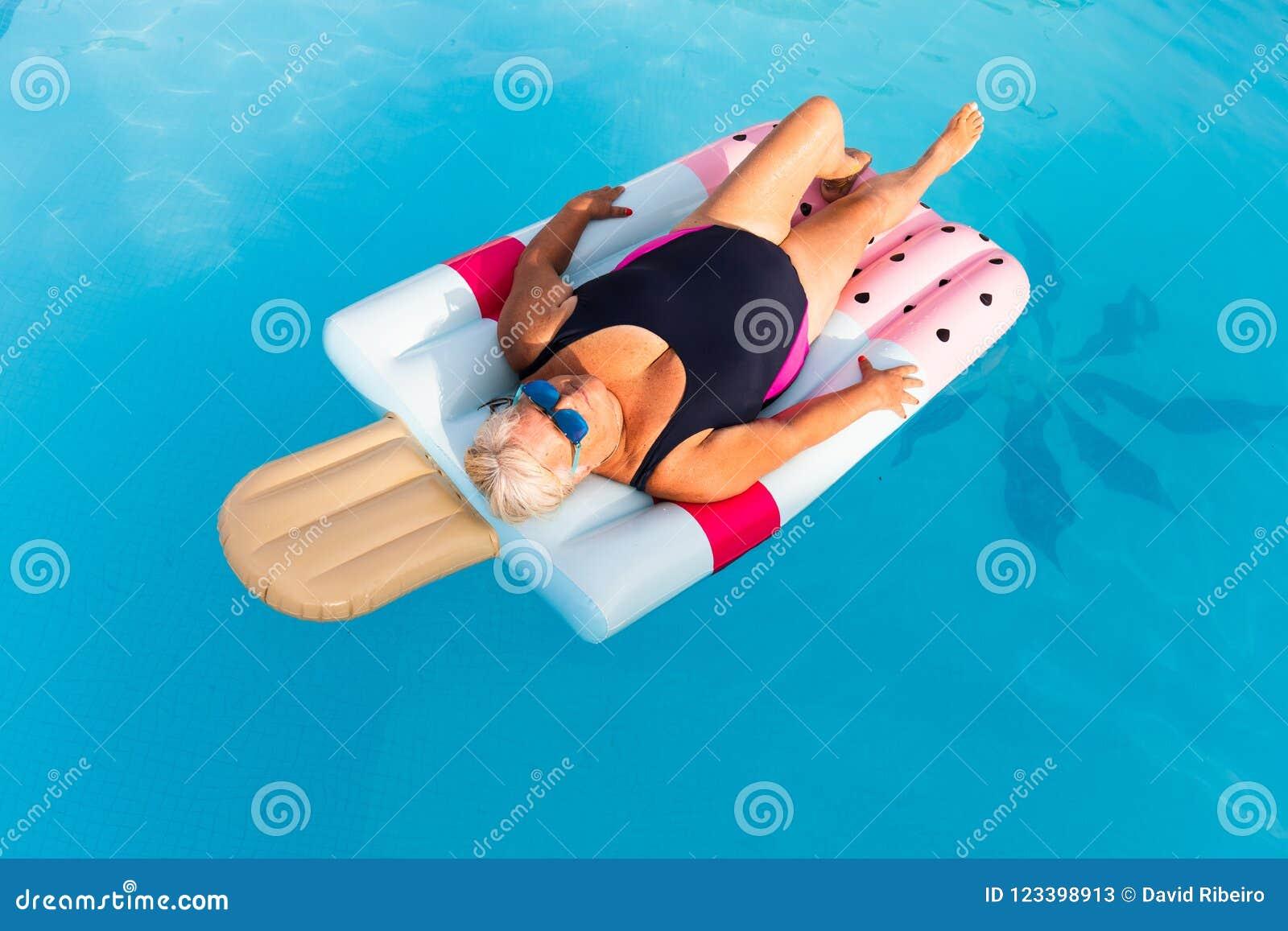 Mulher fêmea superior com mentiras brilhantes dos vidros de sol em um flutuador dado forma da piscina gelado inflável
