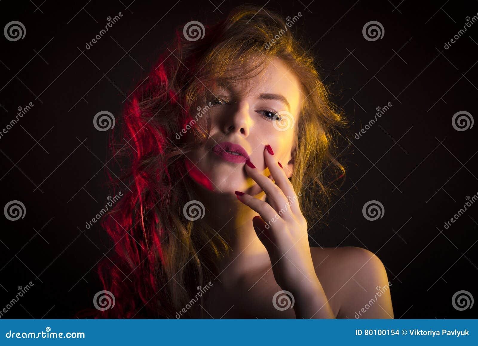 Mulher fabulosa com sombra em suas cara e luz vermelha