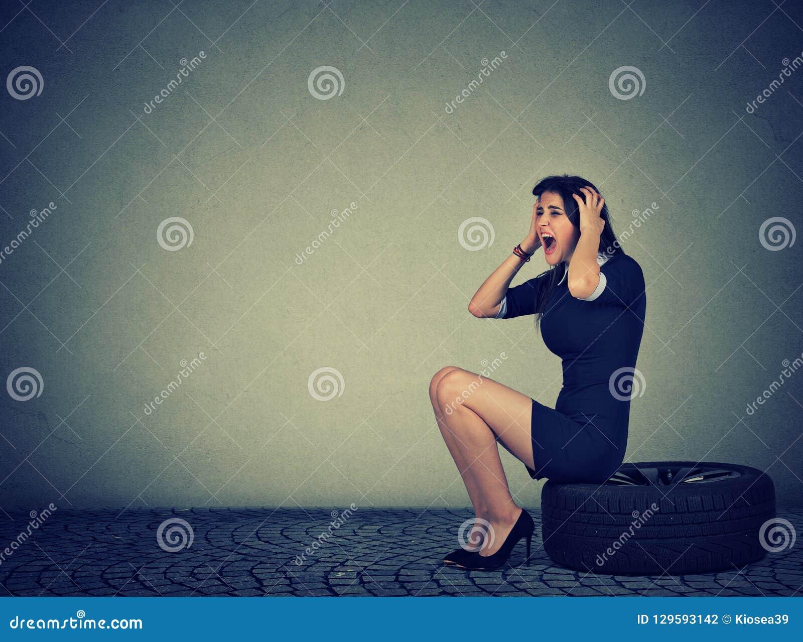 Mulher fatigante que grita ao sentar-se no pneu