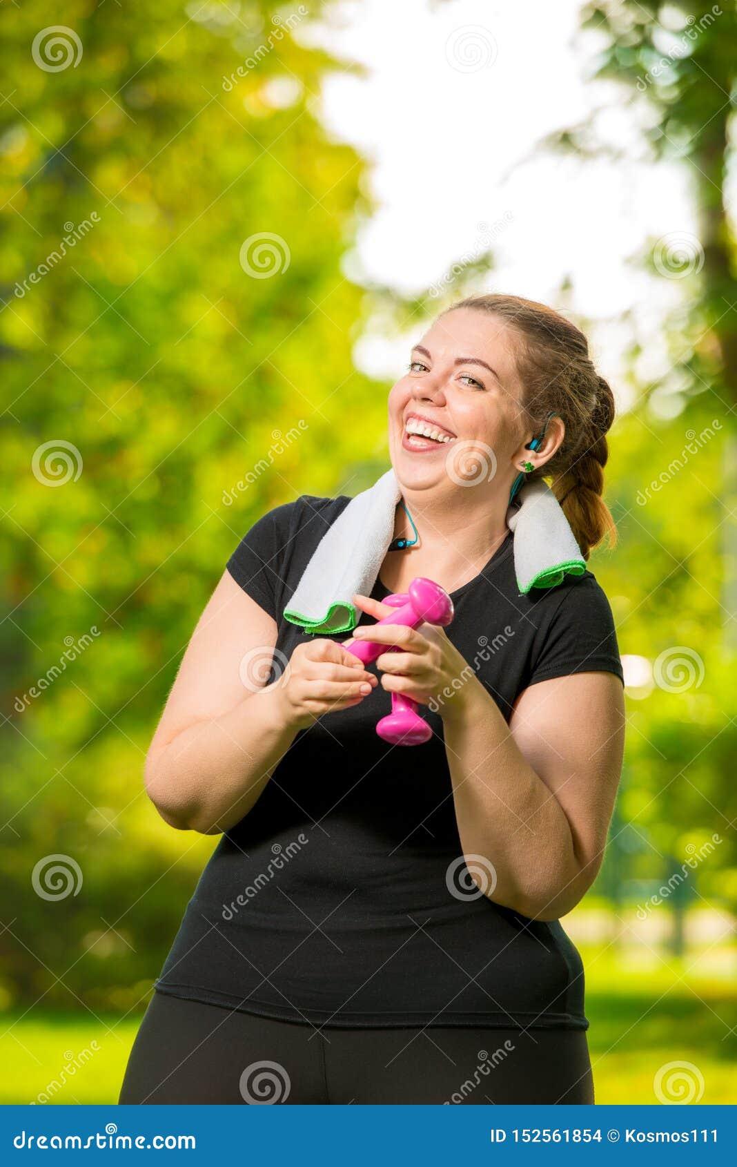 Mulher feliz 30 anos velha mais o tamanho sem negócios dos complexos com pesos durante um exercício