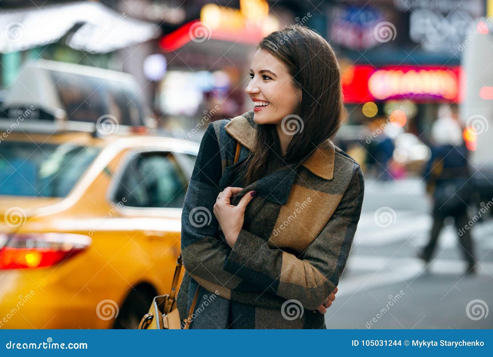 A mulher feliz aprecia a caminhada no tempo de inverno na rua e em fazer de New York City a compra do Natal