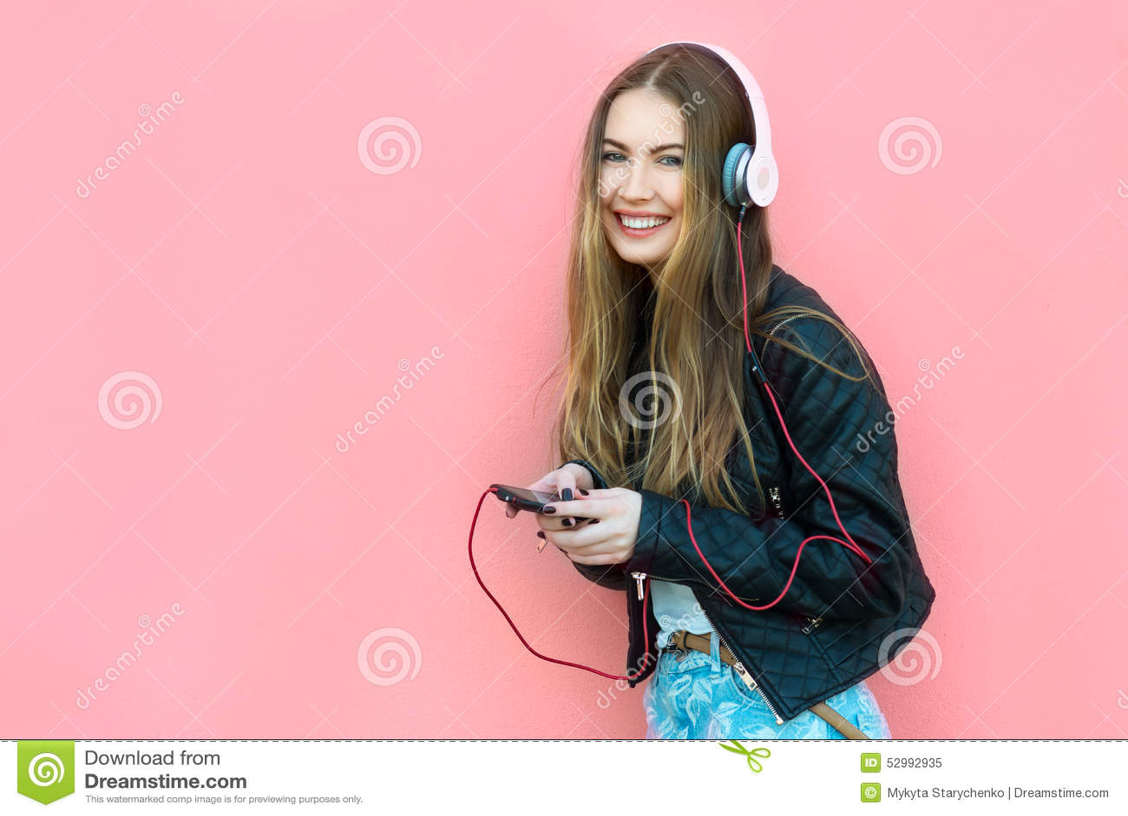 Mulher feliz bonita na música de escuta dos fones de ouvido perto da parede