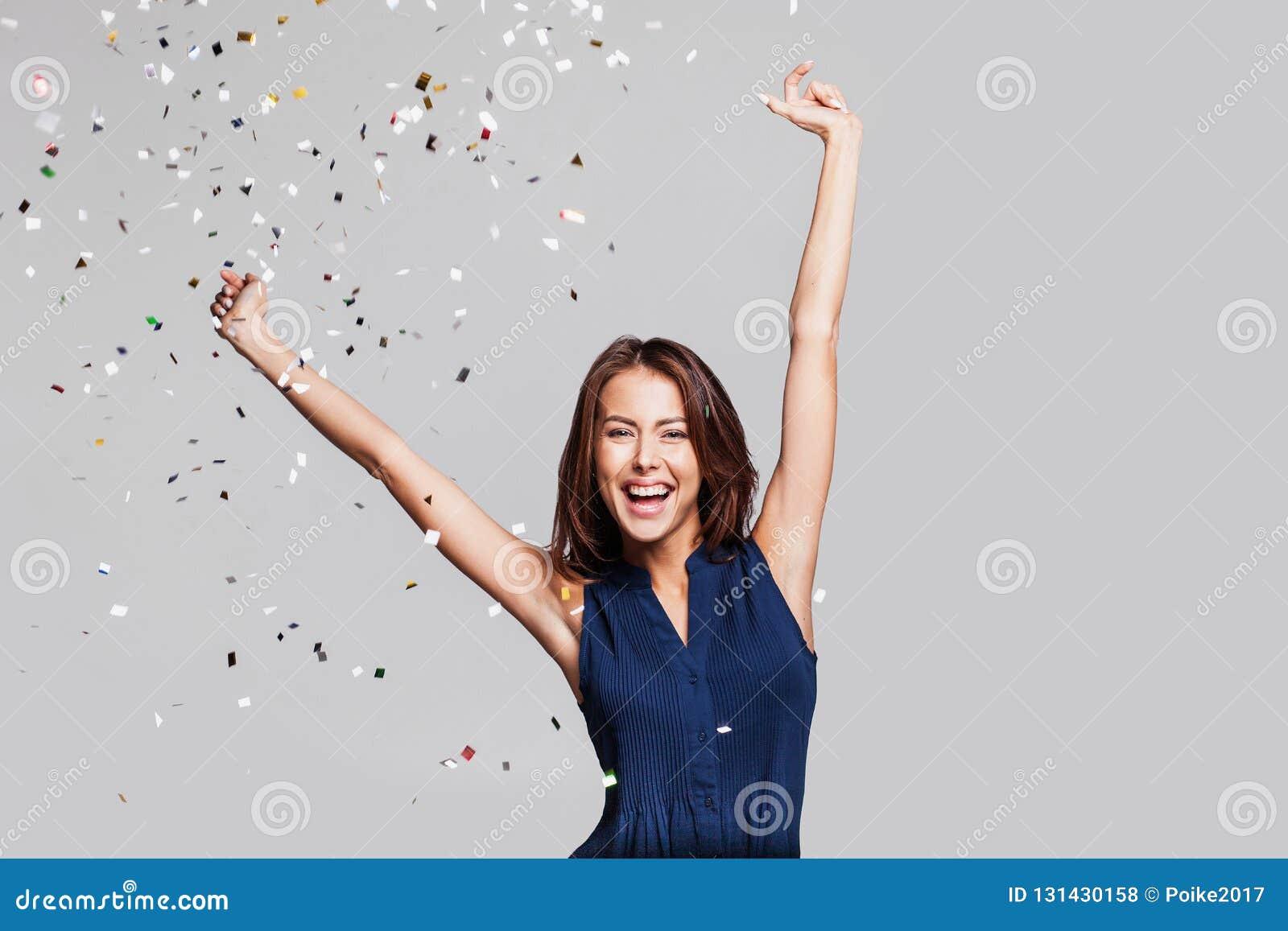 Mulher feliz bonita no partido da celebração com os confetes que caem em toda parte nela Véspera do aniversário ou de ano novo qu