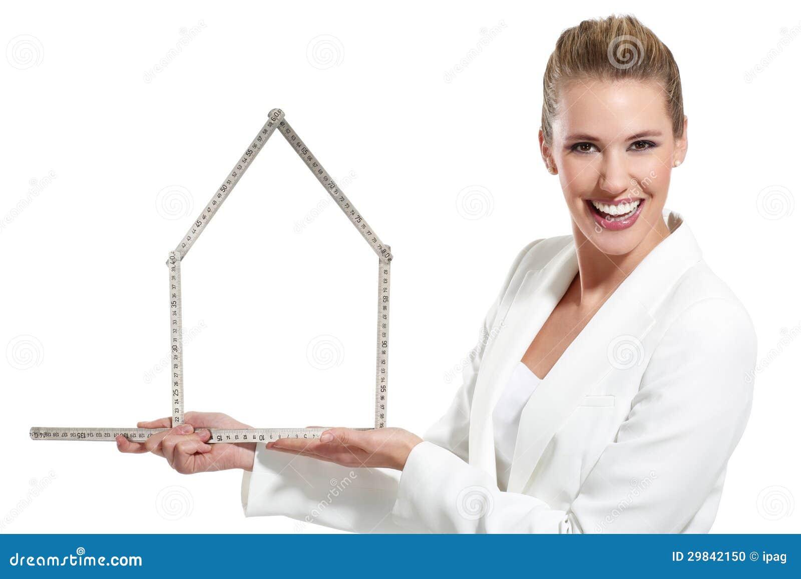 Mulher feliz bonita que mostra um símbolo da casa