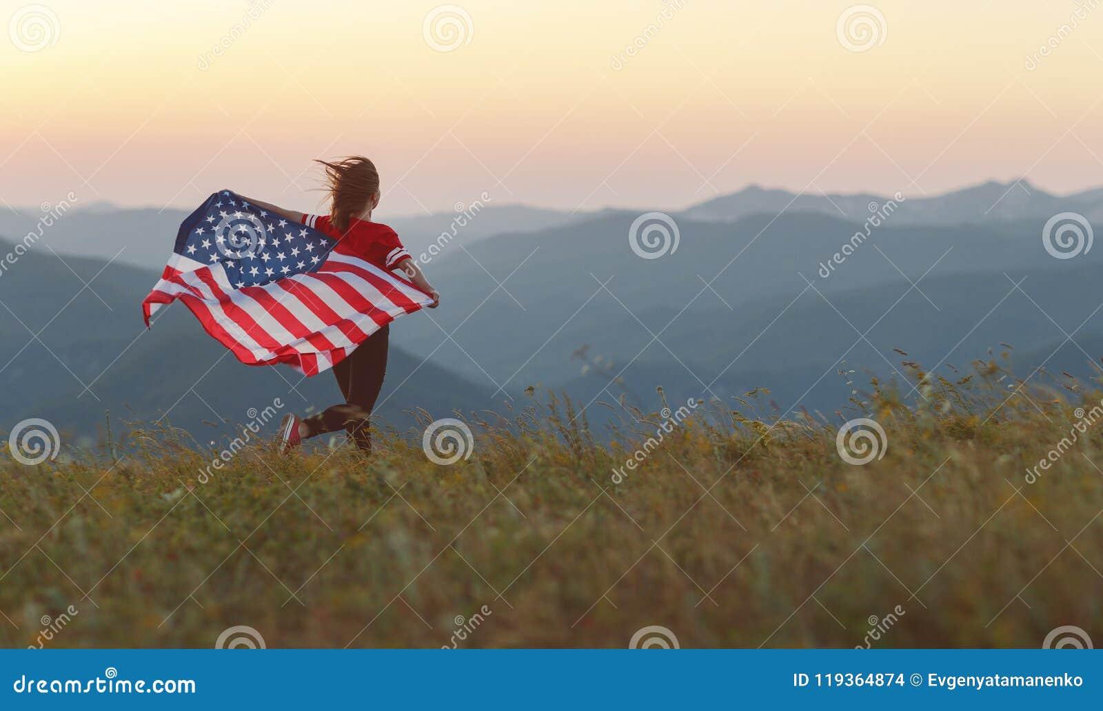 Mulher feliz com a bandeira de Estados Unidos que aprecia o por do sol no na