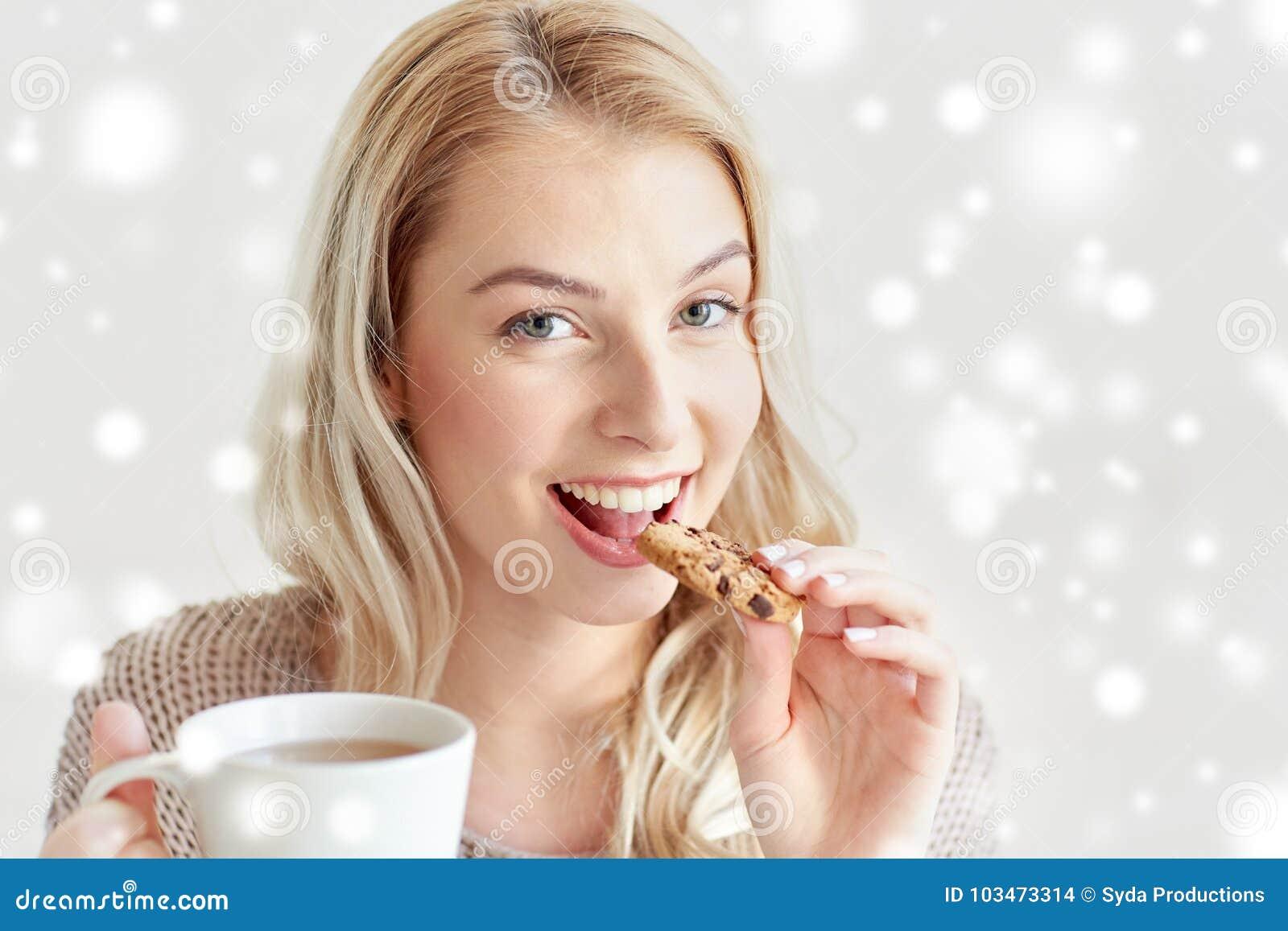 Mulher feliz com chá que come a cookie no inverno