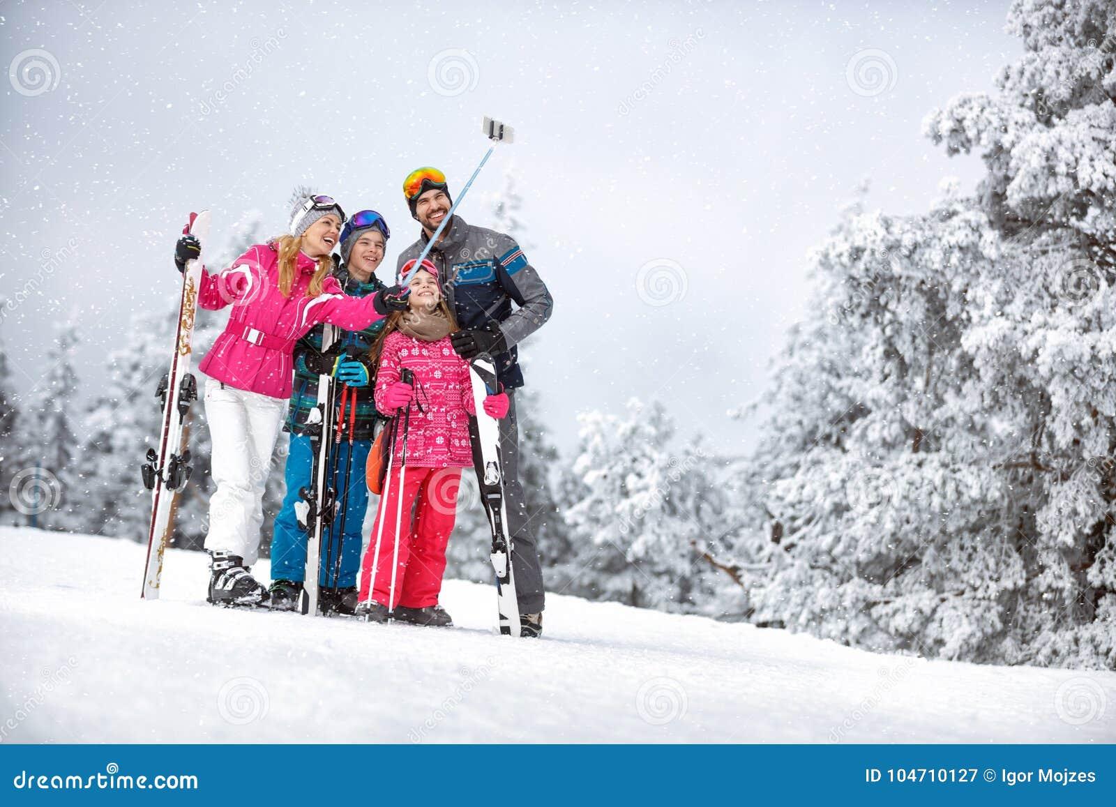 Mulher feliz com a família que faz o selfie na montanha